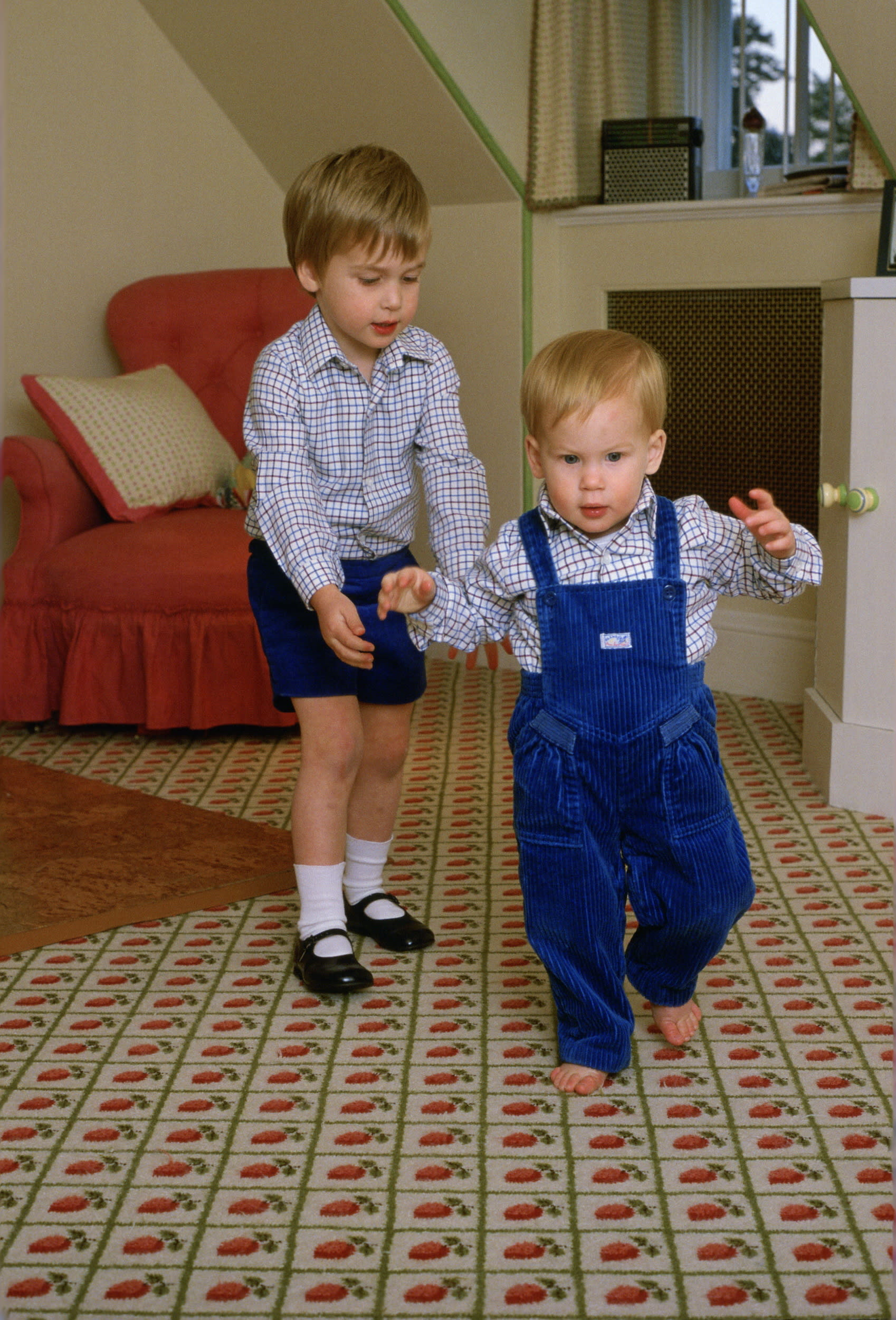 LONDON, UNITED KINGDOM - OCTOBER 22:  Prince William Standing Behind His Brother, Prince Harry, To Help Him As He Tries To Walk On His Own In The Playroom At Kensington Palace  (Photo by Tim Graham/Getty Images)