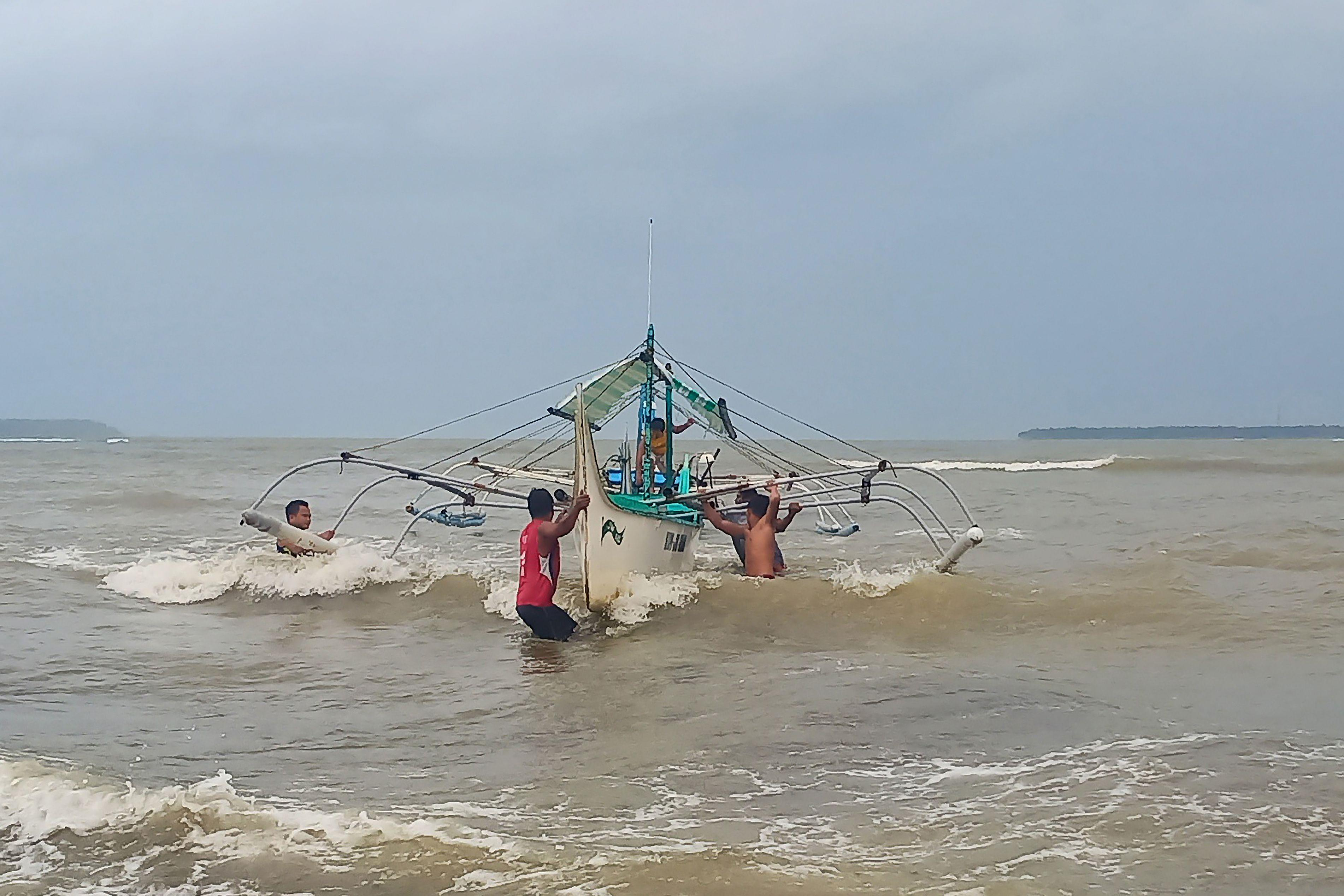 Residents help carry a wooden fishing boat into a secured area along the coast in Borongan town, Eastern Samar province, central Philippines, on December 2, 2019, as they prepare for Typhoon Kammuri. - The Philippines was braced for powerful Typhoon Kammuri as the storm churned closer, forcing evacuations and threatening plans for the Southeast Asian Games events near the capital Manila. (Photo by Alren BERONIO / AFP) (Photo by ALREN BERONIO/AFP via Getty Images)