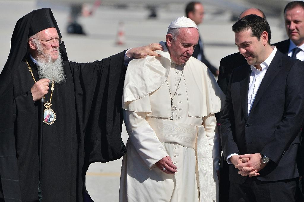 Greek Prime Minister Alexis Tsipras (R) and Bartholomew I of Constantinople (L), Archbishop of Constantinople and Ecumenical Patriarch, greet Pope Francis upon his arrival on the Greek island of Lesbos on April 16, 2016