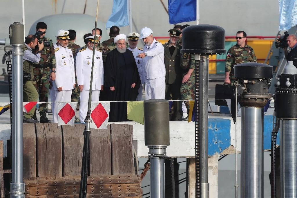 A handout picture provided by Iran's presidency on February 17, 2019, shows Hassan Rouhani (dressed in black) during the unveiling of the country's first semi-heavy submarine at Bandar Abbas naval base