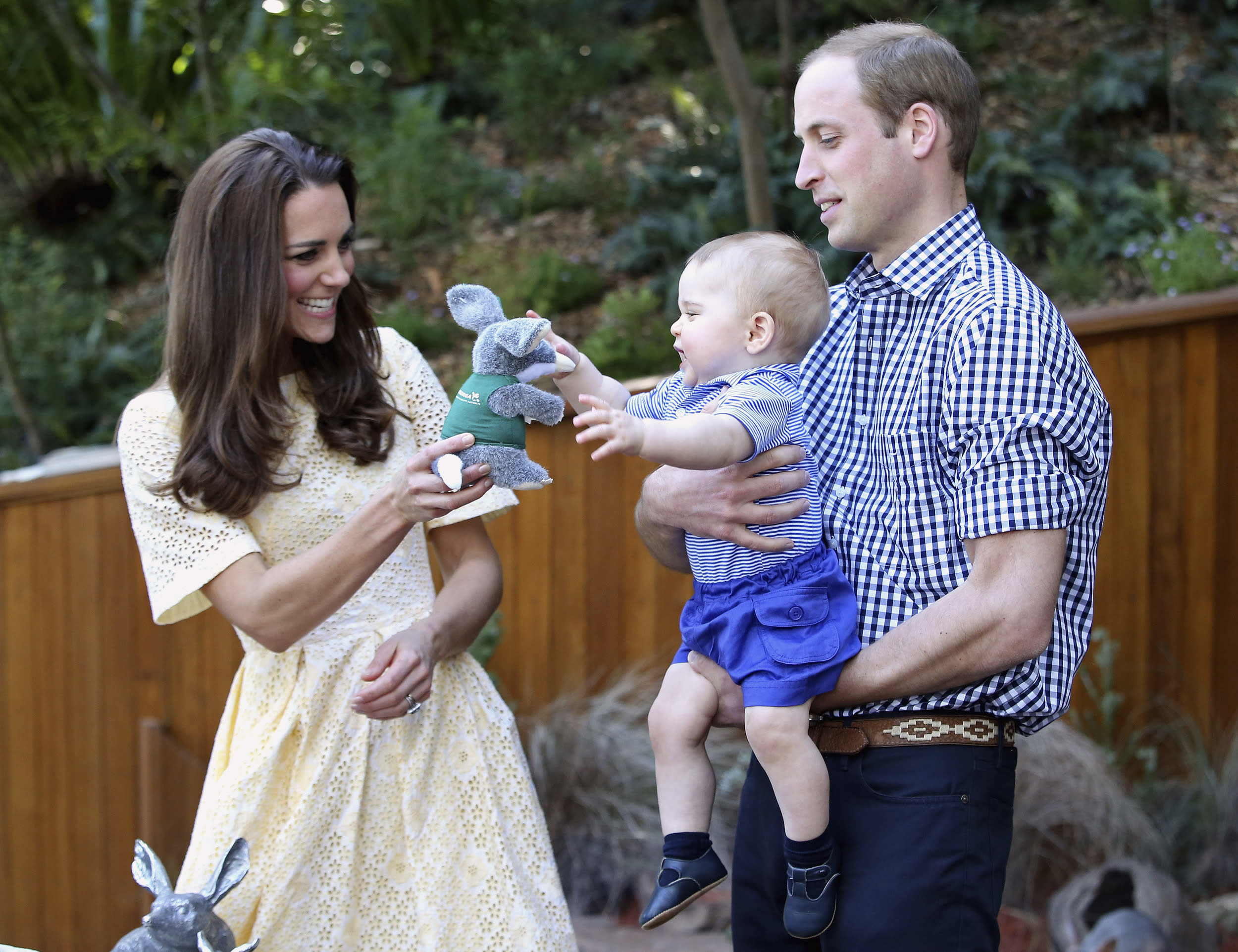Prince William holds Prince George as Catherine, Duchess of Cambridge, gives him a toy during a visit to the Bilby Enclosure at Sydney's Taronga Zoo April 20, 2014. The Prince and his wife Kate are undertaking a 19-day official visit to New Zealand and Australia with their son George. REUTERS/Chris Jackson/Pool (AUSTRALIA - Tags: ENTERTAINMENT ROYALS SOCIETY)