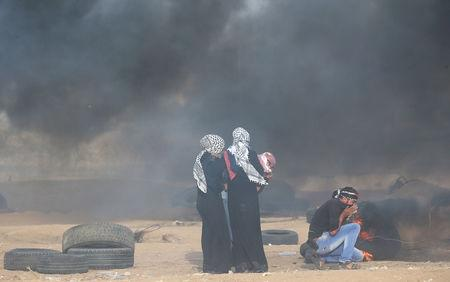 Palestinians react to tear gas fired by Israeli troops during a protest calling for lifting the Israeli blockade on Gaza and demanding the right to return to their homeland, at the Israel-Gaza border fence in the southern Gaza Strip October 5, 2018. REUTERS/Ibraheem Abu Mustafa
