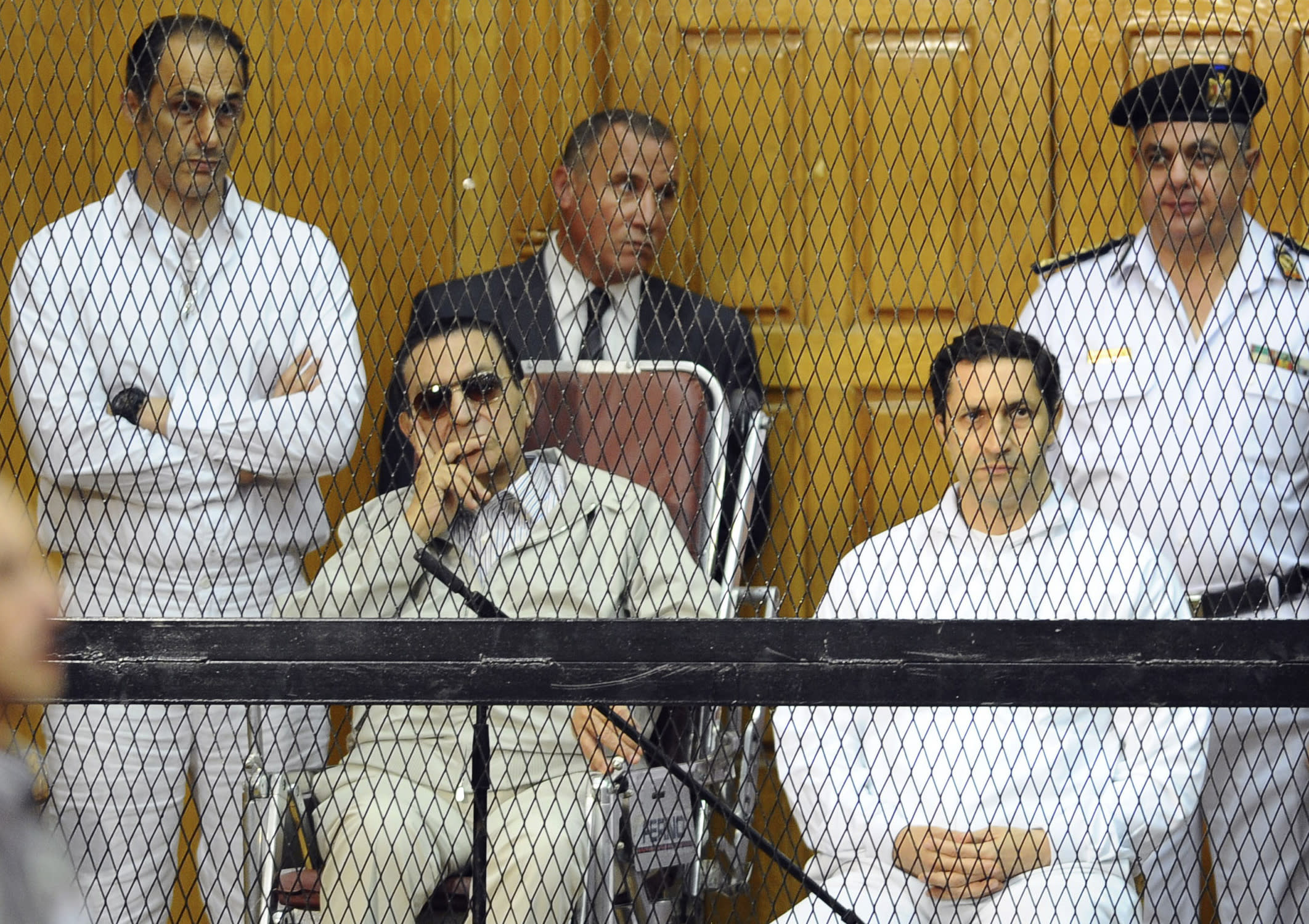 FILE - In this Sept. 14, 2013 file photo, former Egyptian President Hosni Mubarak, seated center left, and his two sons, Gamal Mubarak, left, and Alaa Mubarak attend a hearing in a courtroom in Cairo, Egypt. An Egyptian court on Thursday, Sept. 20, 2018 ordered the release from detention of former president Hosni Mubarak's two sons who are on trial on insider trading charges. (AP Photo/Mohammed al-Law, File)