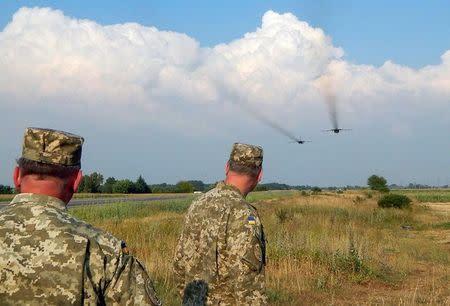 Ukrainian servicemen watch Sukhoi Su-24 front-line bombers fly during military aviation drills as Russia accuses Ukraine in incursion into annexed Crimea, in Rivne region, Ukraine, August 10, 2016. Picture taken August 10, 2016. REUTERS/Stringer