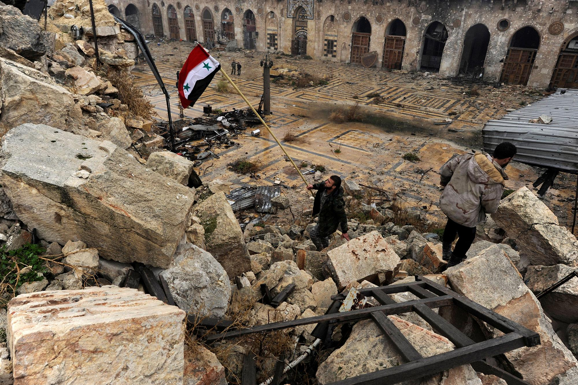 <p>A member of forces loyal to Syria's President Bashar al-Assad attempts to erect the Syrian national flag inside the Umayyad mosque, in the government-controlled area of Aleppo, during a media tour, Syria on Dec.13, 2016. (Photo: Omar Sanadiki/Reuters) </p>