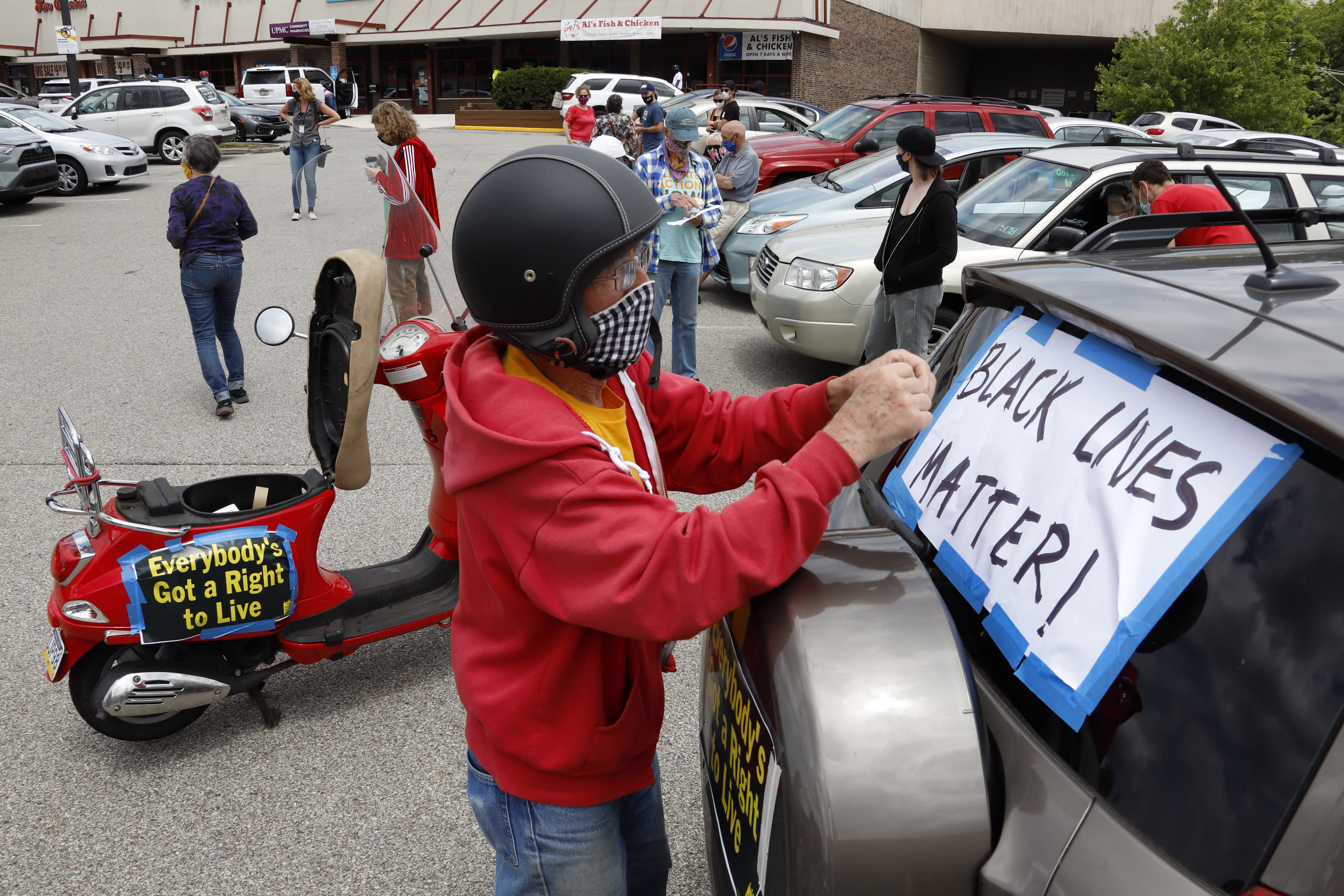 FILE - In this June 14, 2020, file photo, Mel Packer of Pittsburgh tapes a sign on a vehicle in the parking lot of a Shop & Save in downtown Pittsburgh in preparation for the Pennsylvania Poor People's Campaign: National Call for Moral Revival. A national coalition of labor unions, along with racial and social justice organizations, will stage a mass walkout from work July 20, as part of an ongoing reckoning on systemic racism and police brutality in the U.S. (AP Photo/Gene J. Puskar, File)