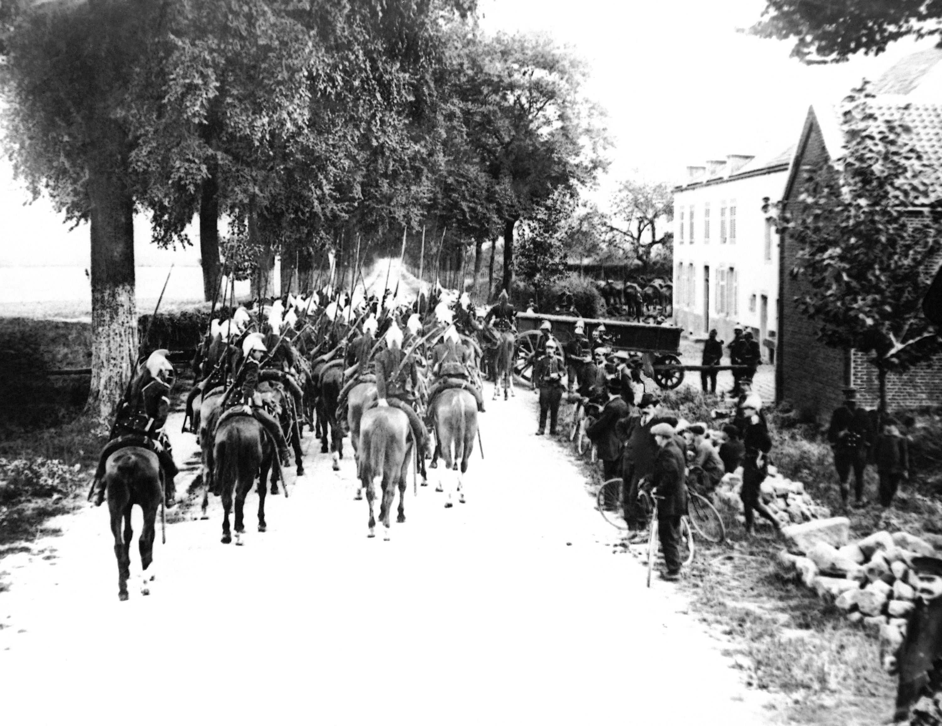FILE - Lancers on horseback enter a Belgium village in the first days of the war on the Western Front in a 1914 photo. They were messengers, spies, sentinels and the heavy haulers of World War I, carrying supplies, munitions and food and leading cavalry charges. The horses, mules, dogs and pigeons were a vital part of the Allied war machine, saving countless lives _ and dying by the millions. (AP Photo, File)