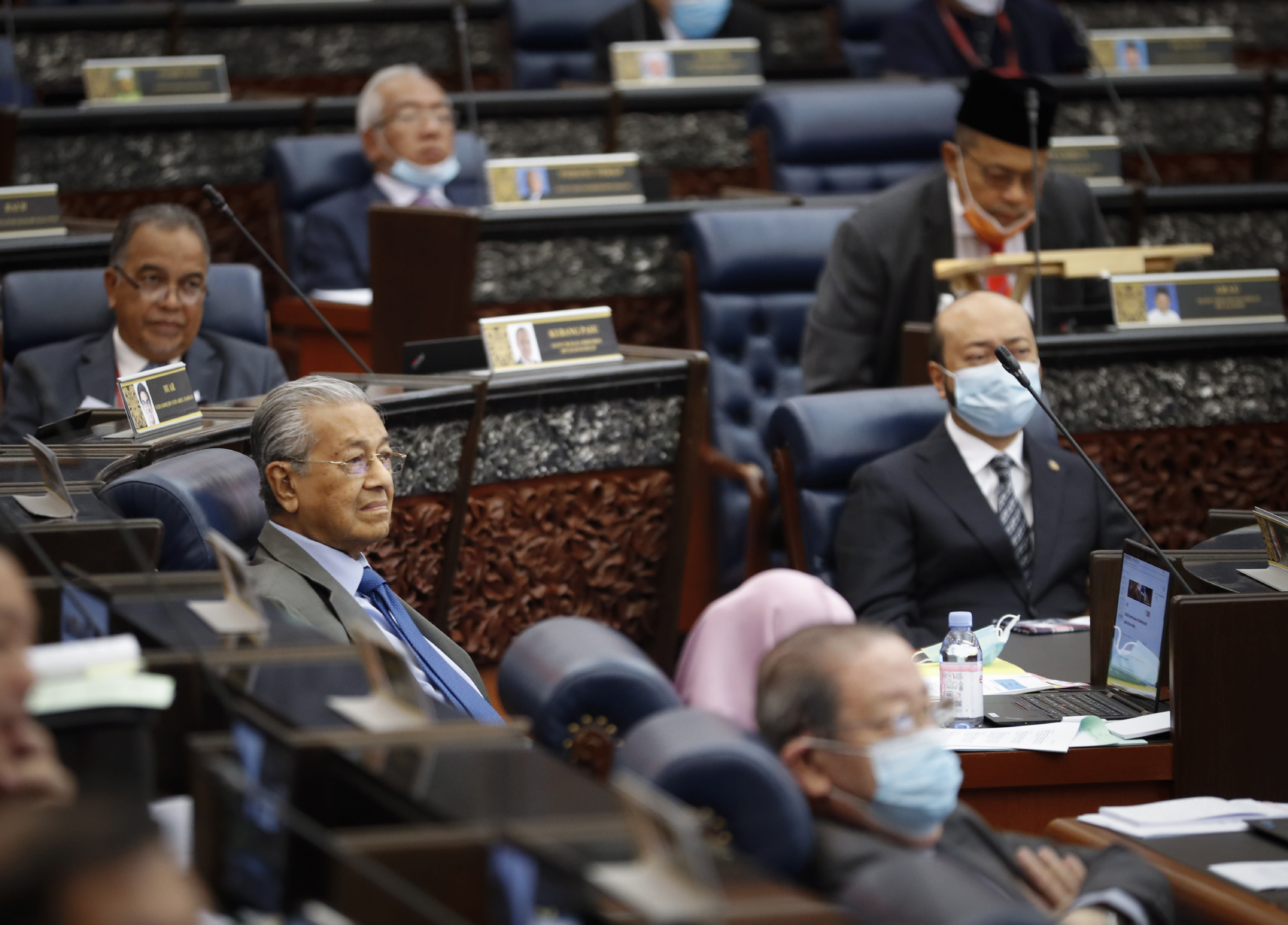 Former Prime Minister Mahathir Mohamad, left, attend a session of the lower house of parliament in Kuala Lumpur, Malaysia, Monday, July 13, 2020. (AP Photo/Vincent Thian)