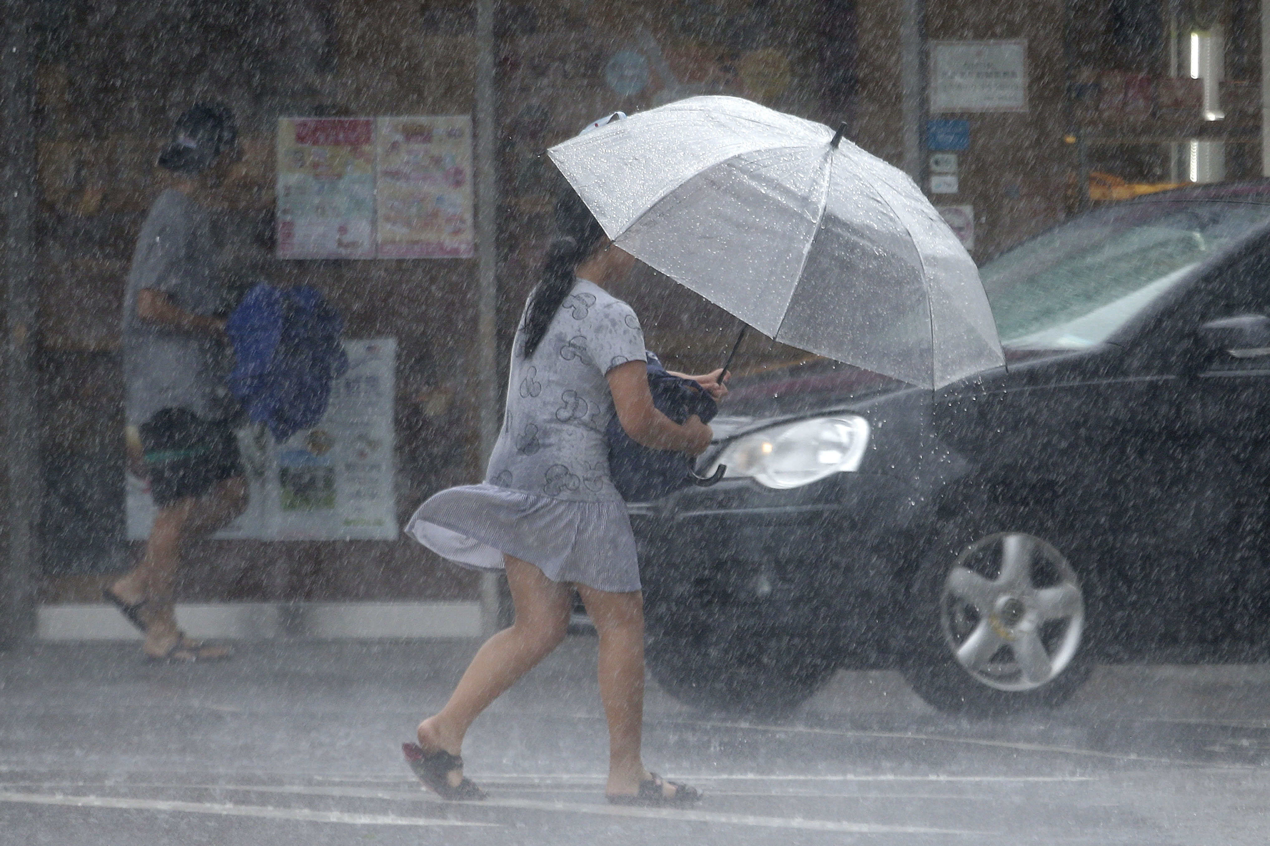 A Taiwanese woman makes her way against powerful gusts of wind generated by typhoon Lekima in Taipei, Taiwan, Friday, Aug. 9, 2019. (AP Photo/Chiang Ying-ying)