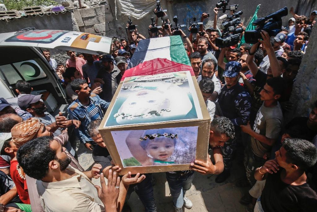 Palestinian mourners carry the coffins of 23-year-old Enas Khammash and her 18-month-daughter Bayan during their funeral in the Gaza Strip on August 9, 2018 after they were killed in an Israeli air strike (AFP Photo/SAID KHATIB)
