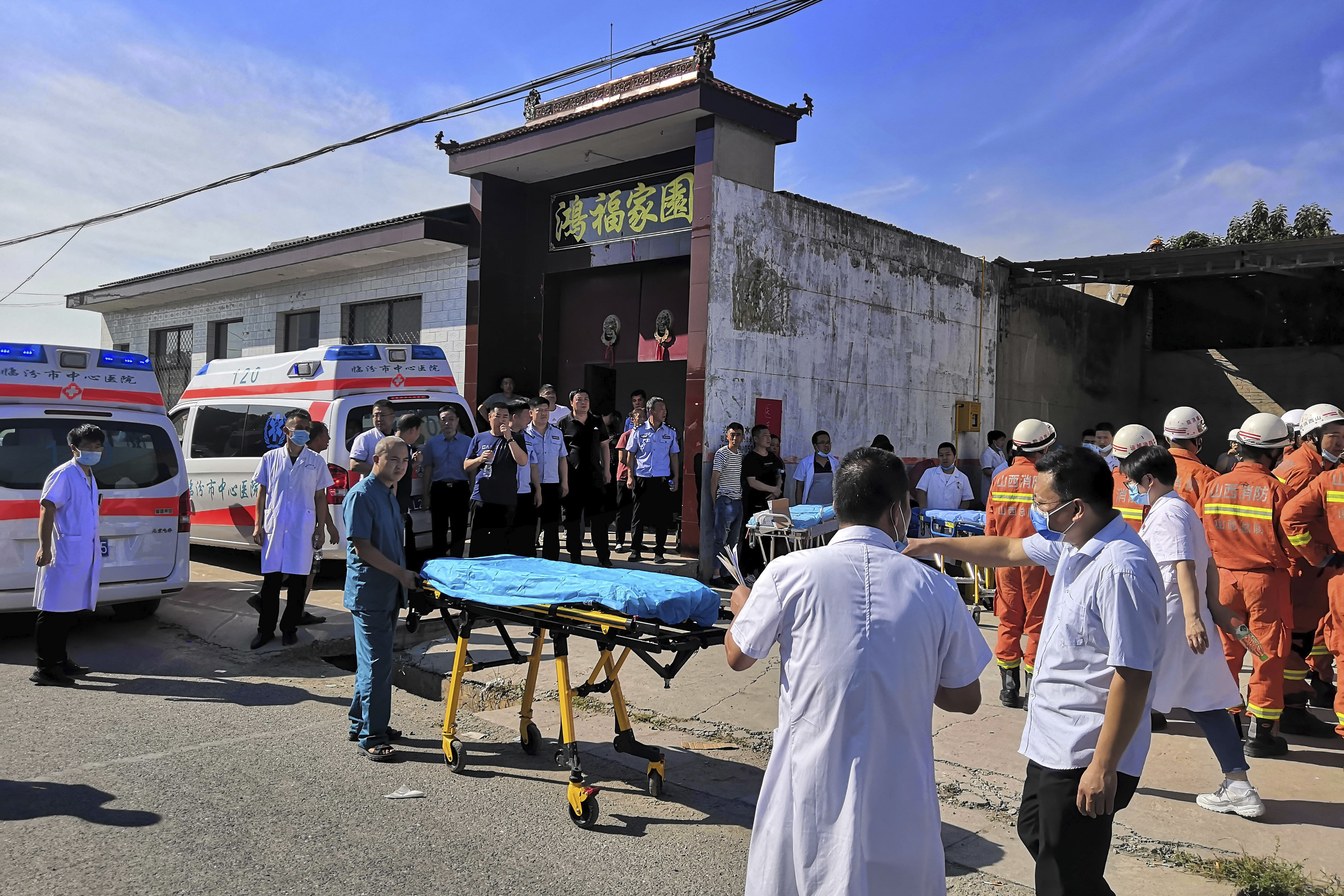 Rescuers and medics gather near the site of a collapsed two-story restaurant in Xiangfen county in northern China's Shanxi province on Saturday, Aug. 29, 2020. More than a dozen were killed after the restaurant collapse during a gathering. (Chinatopix Via AP)