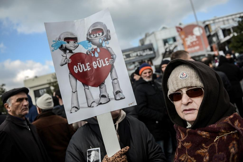 """People hold a sign depicting Koc Holding's mascots and reading """"good bye"""" during Mustafa Koc's funeral on January 24, 2016 in Istanbul (AFP Photo/Ozan Kose)"""