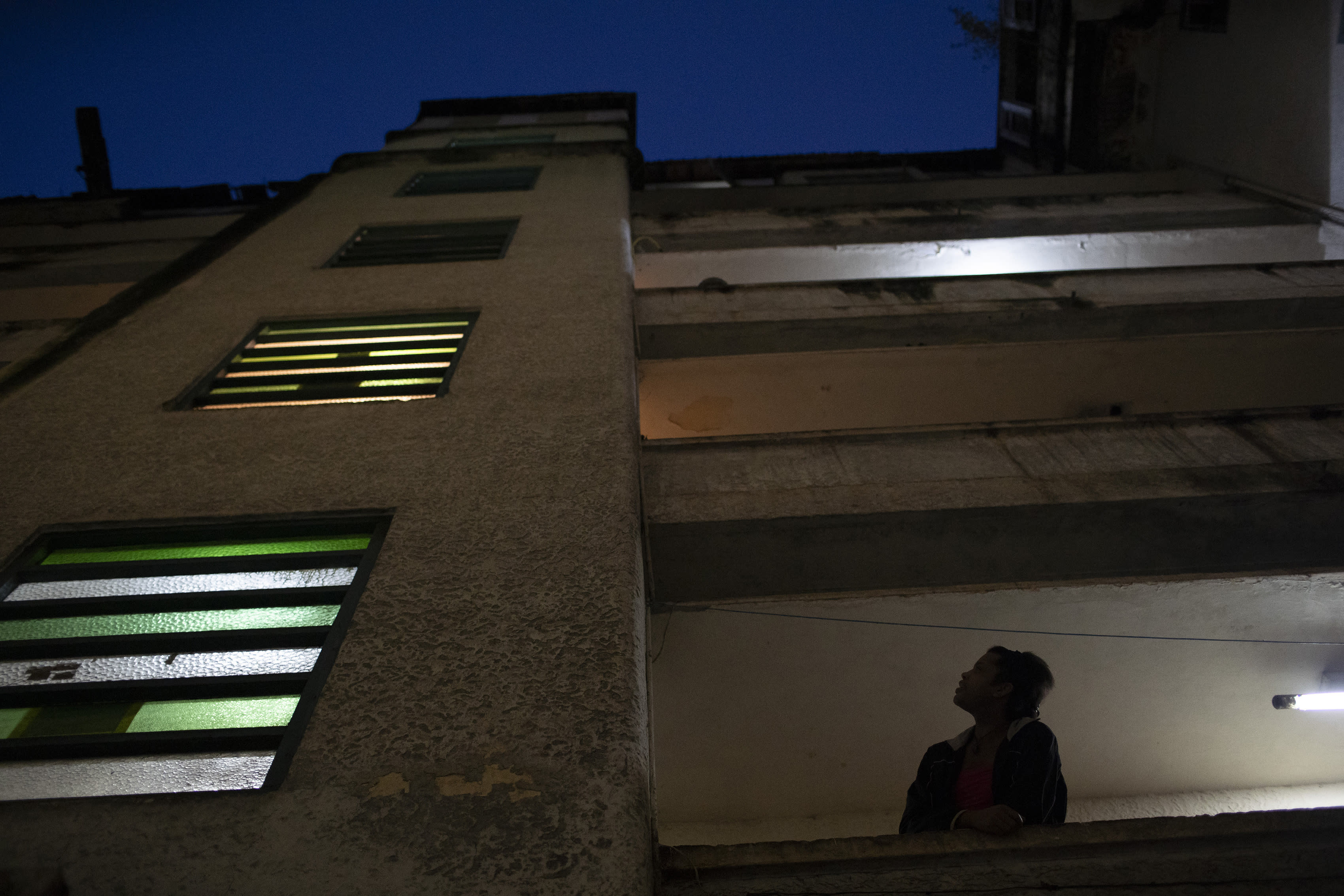 A resident looks up from her balcony at the squat known as Casa Nem, occupied by members of the LGBTQ community who are in self-quarantine as a protective measure against the new coronavirus, in Rio de Janeiro, Brazil, Friday, May 29, 2020. New residents during the pandemic have to isolate on one of the building's floors for 15 days to ensure they don't develop symptoms before fully joining the community. (AP Photo/Silvia Izquierdo)