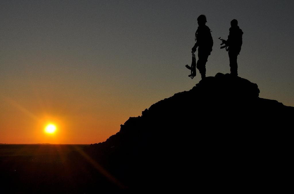 People's Protection Units fighters stand on top of a hill at sunset in Syria's Hasakeh province in February 2015