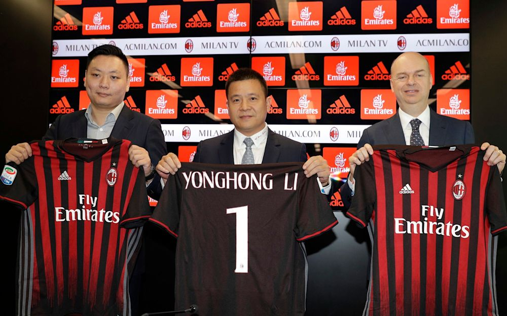 David Han Li, Yonghong Li, and Marco Fassone, pose with AC Milan shirtsng a press conference - AP