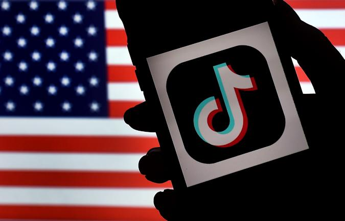 """In this photo illustration, the social media application logo, TikTok is displayed on the screen of an iPhone on an American flag background on August 3, 2020 in Arlington, Virginia. - President Donald Trump said Monday that Chinese-owned hugely popular video-sharing app TikTok will be """"out of business"""" in the United States if not sold to a US firm by September 15, 2020.""""I set a date of around September 15, at which point it's going to be out of business in the United States,"""" he told reporters. (Photo by Olivier DOULIERY / AFP) (Photo by OLIVIER DOULIERY/AFP via Getty Images)"""