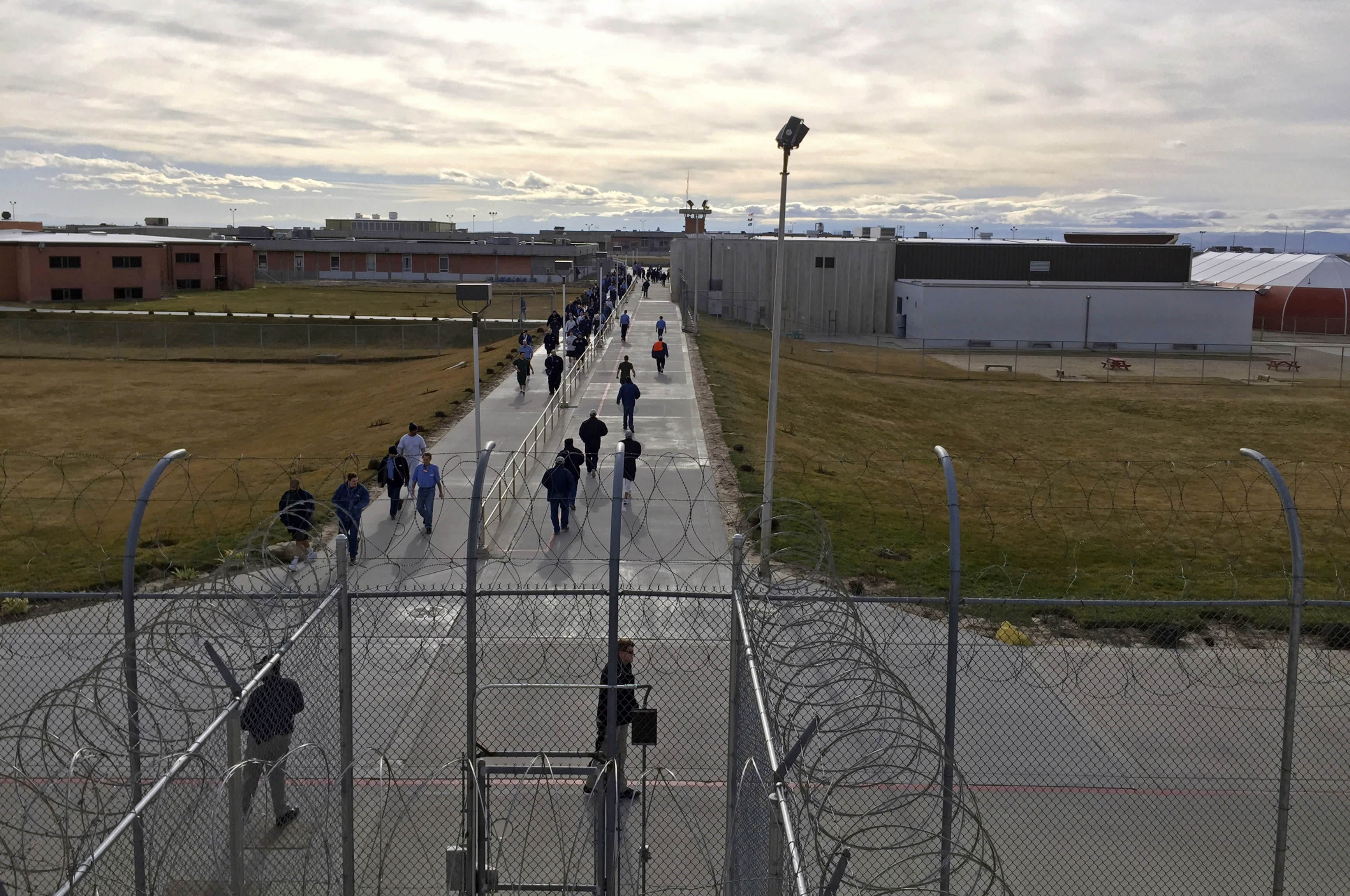 FILE - In this Jan. 30, 2018, file photo, inmates walk across the grounds of the Idaho State Correctional Institution in Kuna, Idaho. Hundreds of thousands of dollars in coronavirus relief payments have been sent to people behind bars across the United States, and now the IRS is asking state officials to help claw back the cash that the federal tax agency says was mistakenly sent. The IRS doesn't yet have numbers on how many payments went to inmates. But initial numbers from some states suggest the numbers are huge: The Kansas Department of Correction alone intercepted more than $200,000 in checks sent to prisoners by early June. Idaho and Montana combined had intercepted over $90,000. (AP Photo/Rebecca Boone, File)