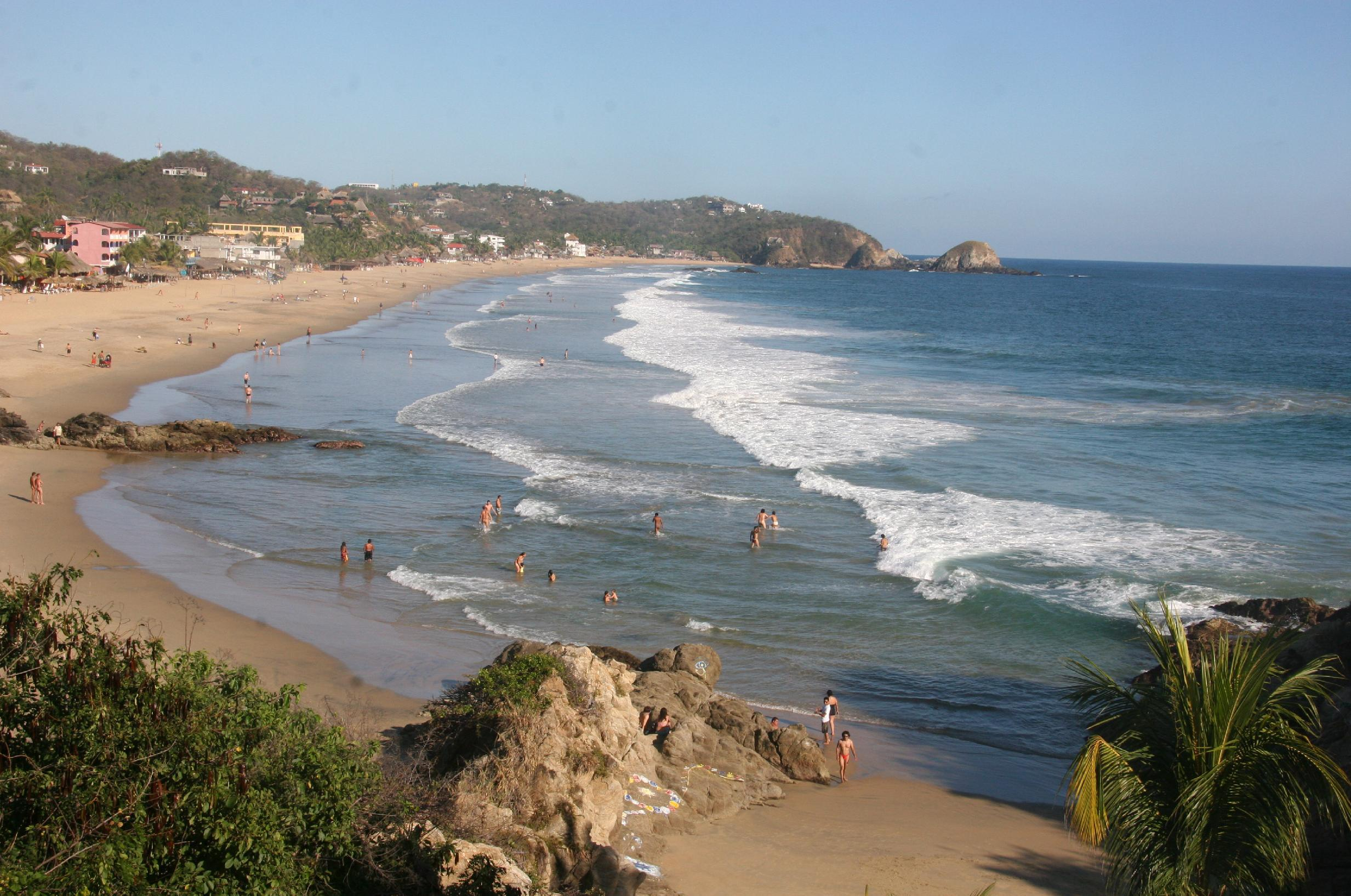 This Jan. 6, 2013 photo shows visitors bathing in the surf along the beach in Zipolite, Mexico. A sleepy town with one main street and no ATMs, Zipolite is one many tiny coastal pueblos that dot the Pacific in Mexico's Southern state of Oaxaca. (AP Photo/Jody Kurash)