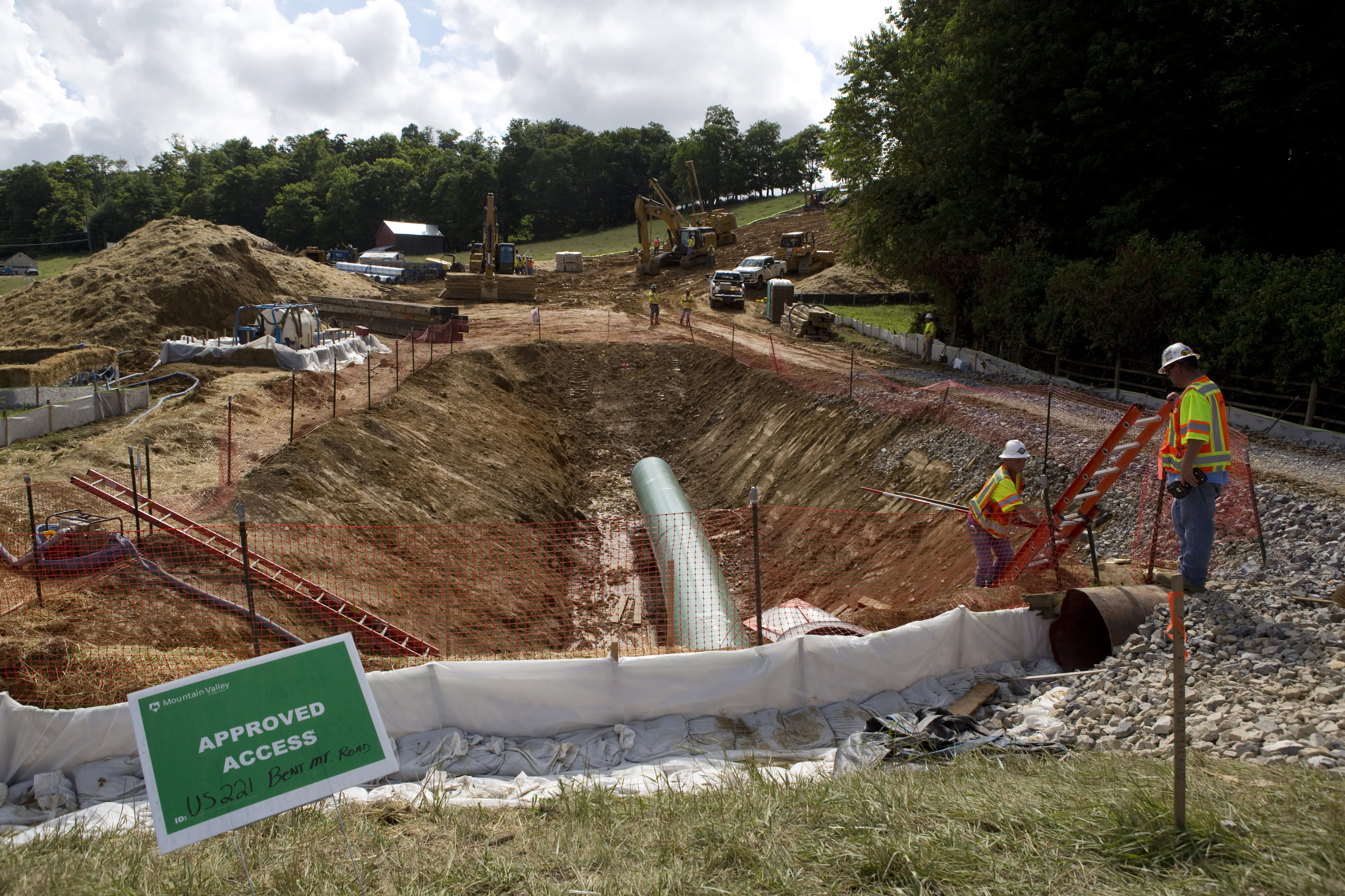 FILE - In this June 22, 2018, file photo, construction crews bore beneath U.S. 221 in Roanoke County, Va., to make a tunnel through which the Mountain Valley Pipeline will pass under the highway. The Trump administration is seeking to fast track environmental reviews of the pipeline and dozens of other energy, highway and other infrastructure projects across the U.S. (Heather Rousseau/The Roanoke Times via AP, File)