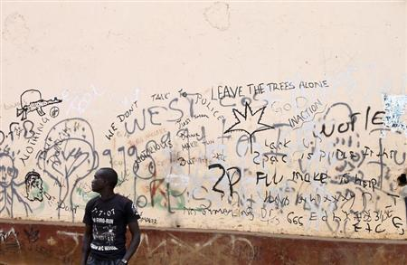 A man stands near graffiti about sex in downtown Kampala
