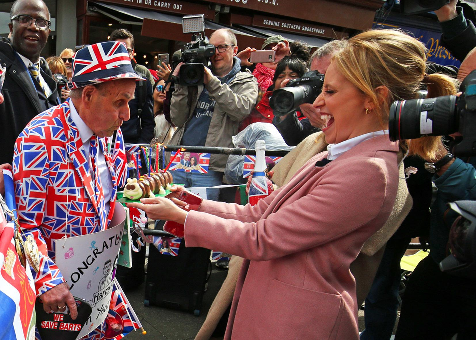 Super fan Terry Hutt, 84 (centre), is presented with a birthday cake by members of the media for a tv stunt in Windsor, Berkshire, following the announcement of the birth of a baby boy to the Duke and Duchess of Sussex.