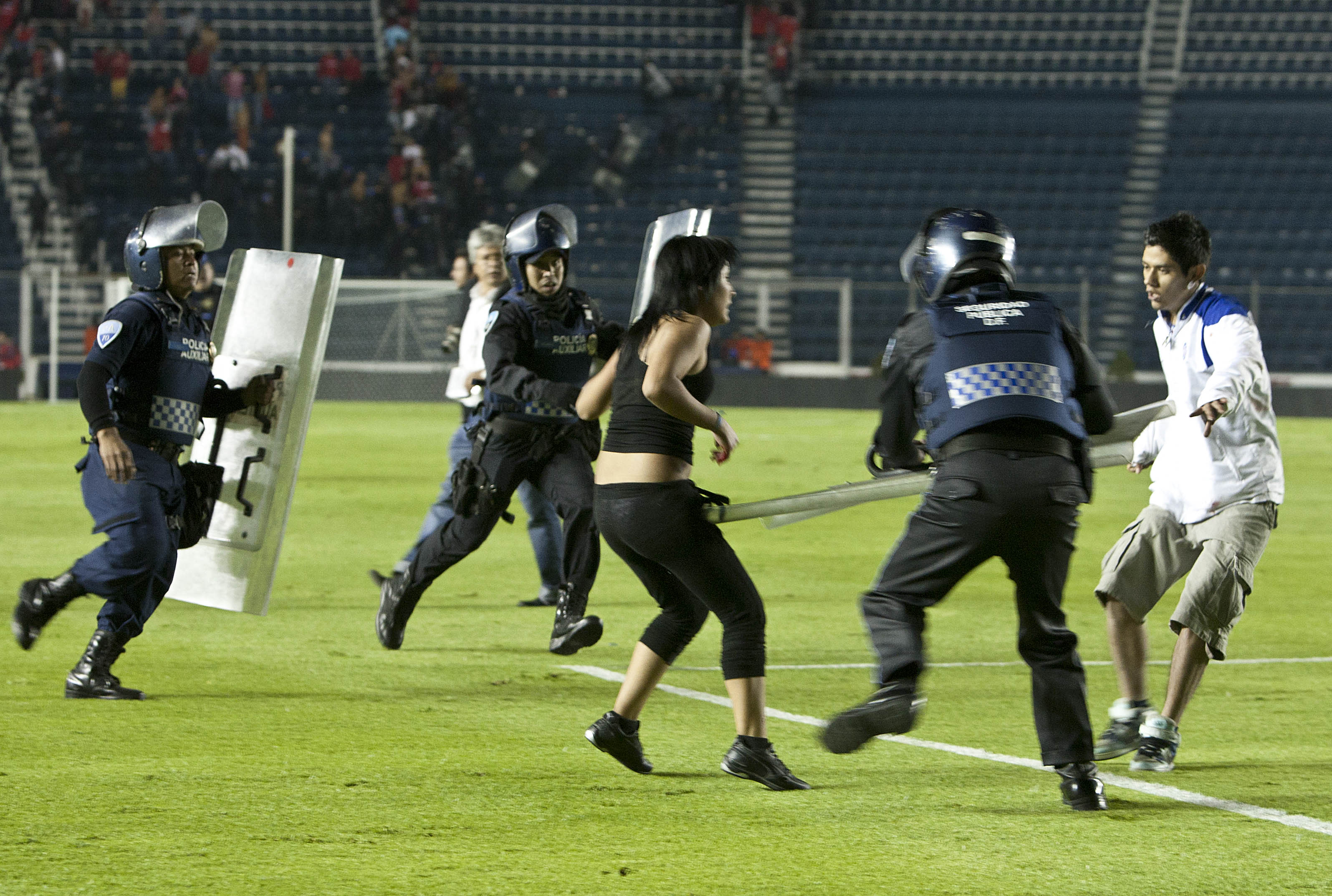 La policía arrincona a un par de aficionados del Cruz Azul que invadieron la cancha luego que su equipo cayó eliminado ante el Toluca en los cuartos de final del torneo Apertura de México, el sábado 30 de noviembre de 2013 (AP Foto/Christian Palma)