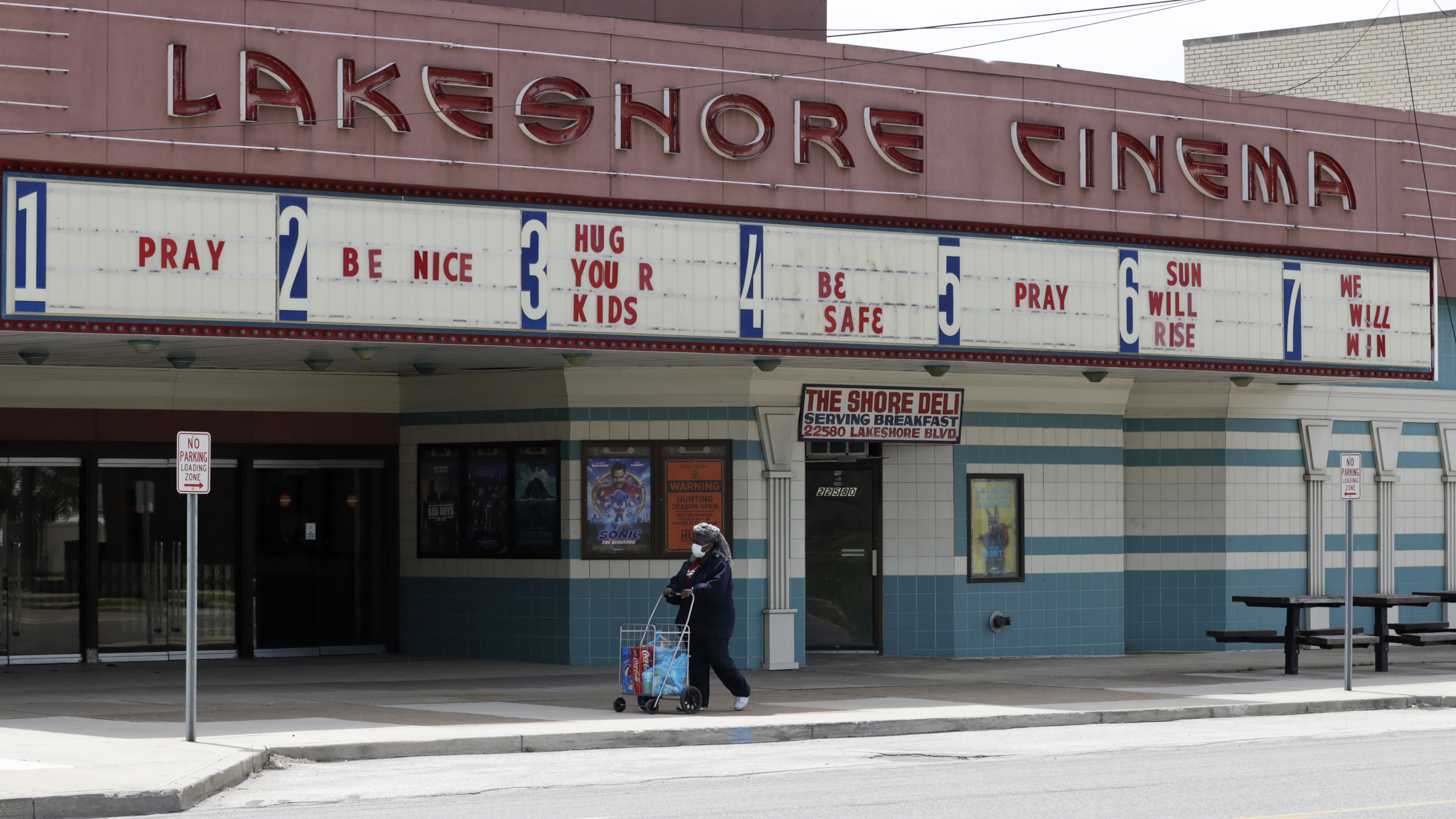 A woman wearing a mask walks with her groceries past a closed Lakeshore Cinema theatre, Wednesday, May 6, 2020, in Euclid, Ohio. With the economy paralyzed by business closures, the unemployment rate likely jumped to at least 16% — from just 4.4% in March — and employers cut a stunning 21 million or more jobs just in April, economists have forecast. (AP Photo/Tony Dejak)