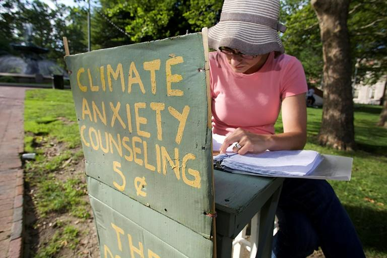 """Kate Schapira, a 40-year-old senior lecturer in the English department at Brown University, mans her """"climate anxiety"""" booth in Providence (AFP Photo/Lara Henderson)"""
