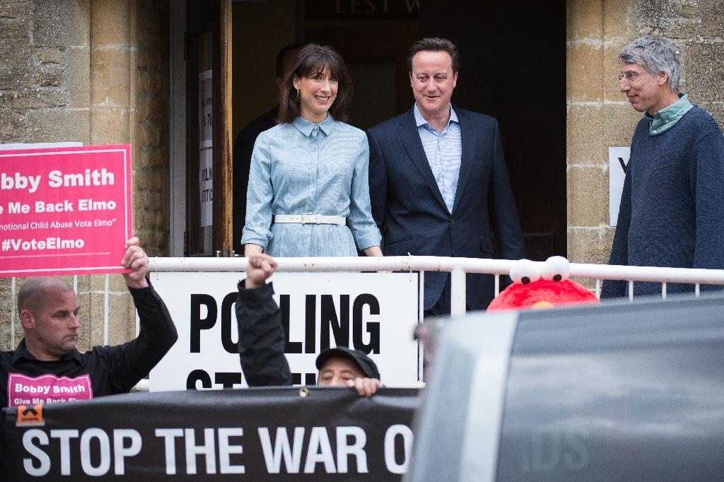 Protestors demonstrate as British Prime Minister and leader of the Conservative party David Cameron leaves with his wife Samantha after voting at a polling station in Spelsbury on May 7, 2015 (AFP Photo/Leon Neal)