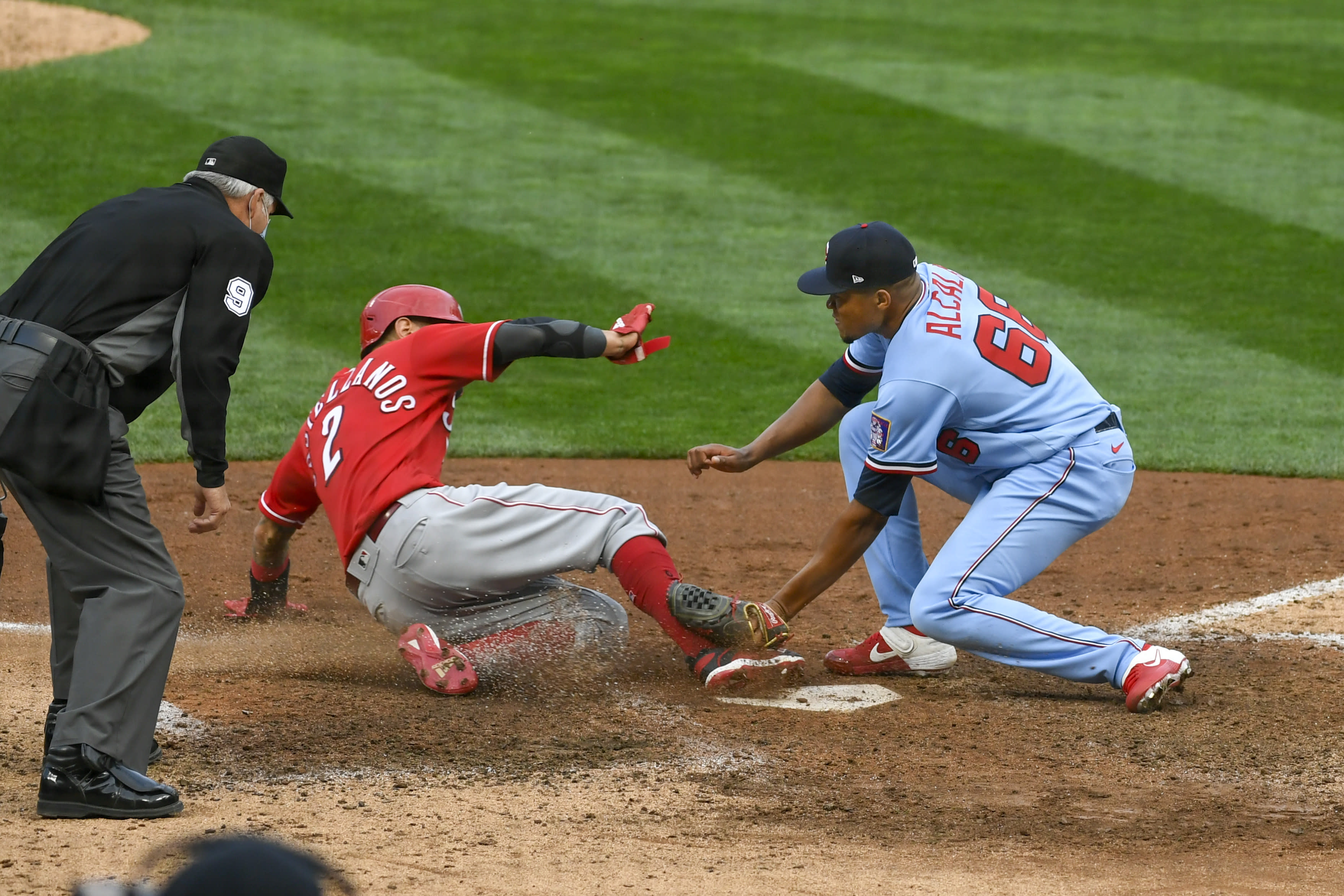 Minnesota Twins pitcher Jorge Alcala, right, tags out Cincinnati Reds' Nick Castellanos as he tries to steal home on a wild pitch during the tenth inning of a baseball game Sunday, Sept. 27, 2020, in Minneapolis. The Reds won 5-3. (AP Photo/Craig Lassig)