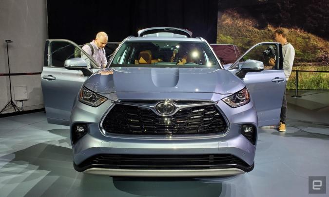 A front-view of a Toyota vehicle on display at the New York Auto Show, with doors open and people looking in.