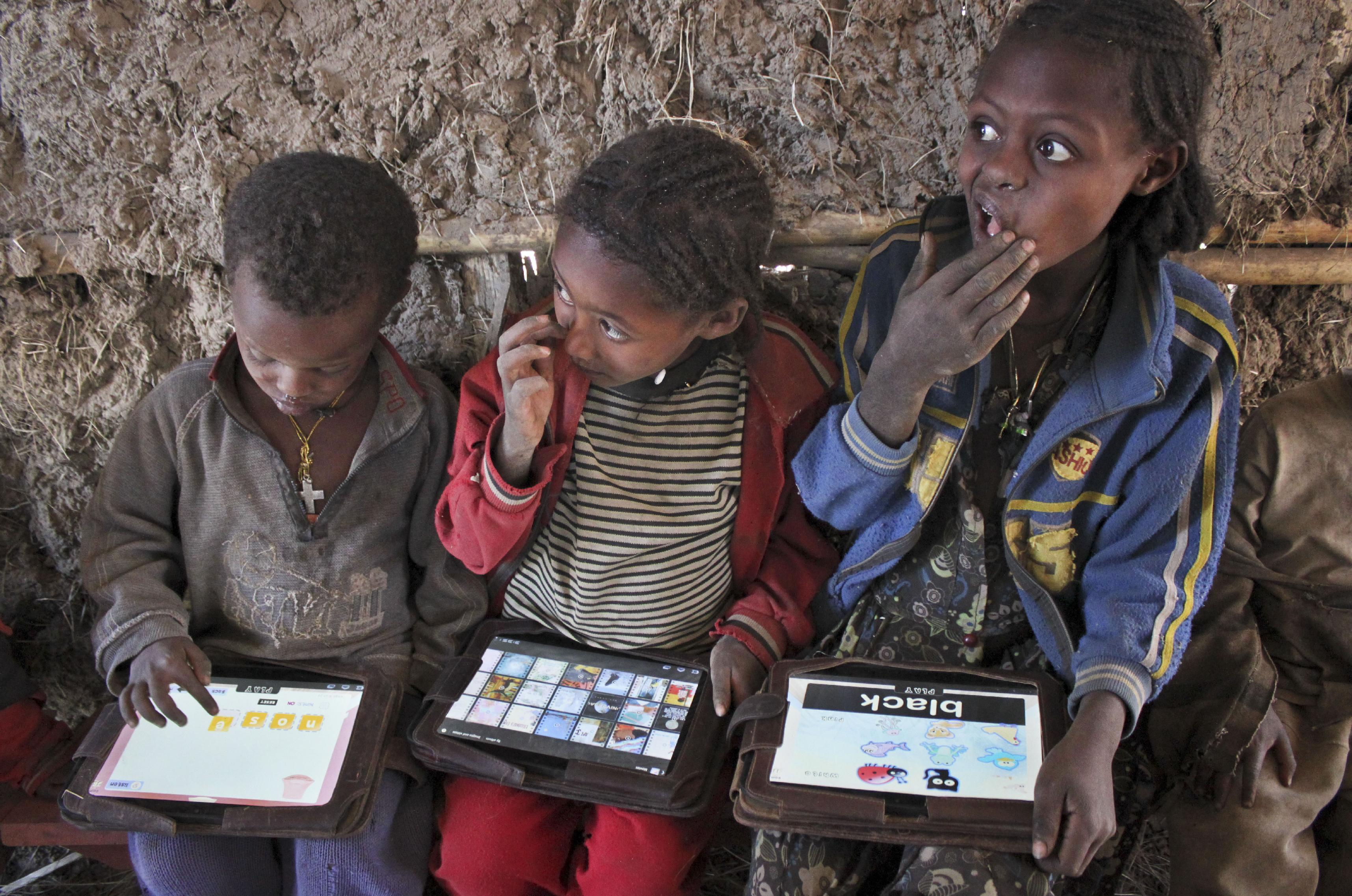 In this photo taken Tuesday, Nov. 27, 2012, children play with tablet computers given to them by the One Laptop Per Child project in the village of Wenchi, Ethiopia. The project gave tablets to the children in the poor, illiterate village to see how much the children could teach themselves and now many kids can recite the English alphabet and spell words in English. (AP Photo/Jason Straziuso)