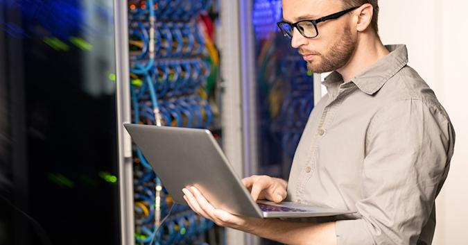 Stock image of a man in front of a server bank, using a laptop while standing up.