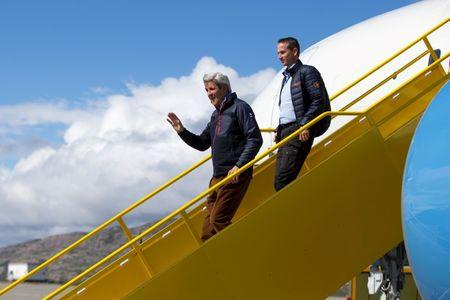 U.S. Secretary of State John Kerry waves as he arrives in Greenland with Danish Foreign Minister Kristian Jensen for a tour of the Illulissat Icefjord and Jakobshavn Glacier