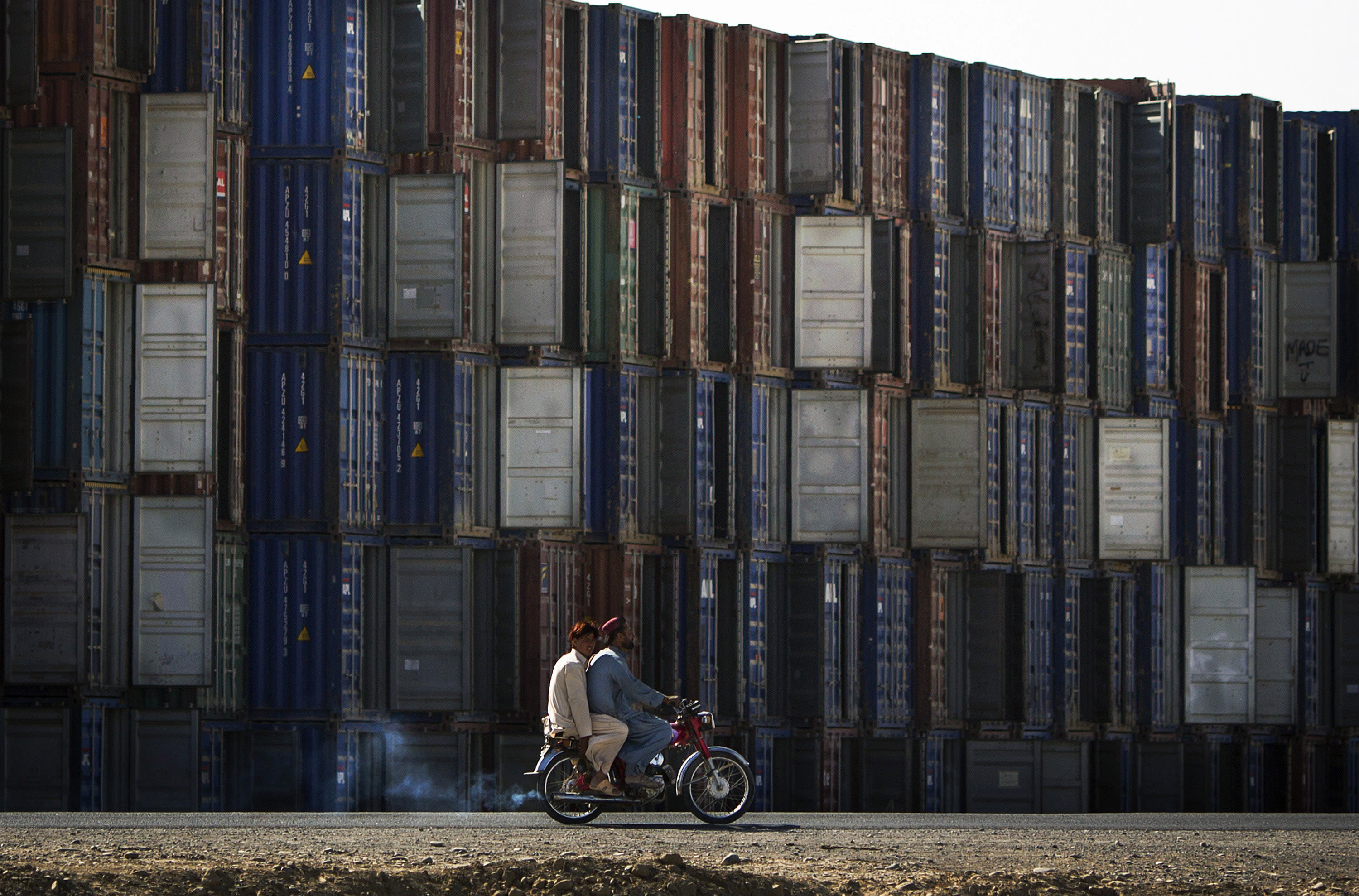 In this Monday, Oct. 28, 2013 photo, two Afghan men on a motorcycle drive by stacks of shipping containers belonging to the U.S. and NATO military in Kandahar, southern Afghanistan. Hundreds of shipping containers are being collected by Afghans, some of which will be eventually scrapped as U.S. and NATO troops prepare to withdrawal all its combat troops by the end of 2014. (AP Photo/Anja Niedringhaus)