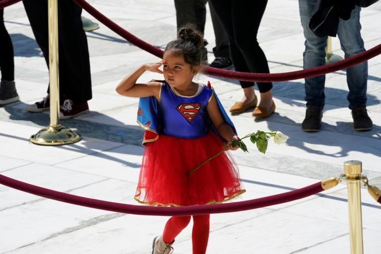 A child in a Supergirl costume pays respects as the late justice Ruth Bader Ginsburg lies in repose in front of the US Supreme Court