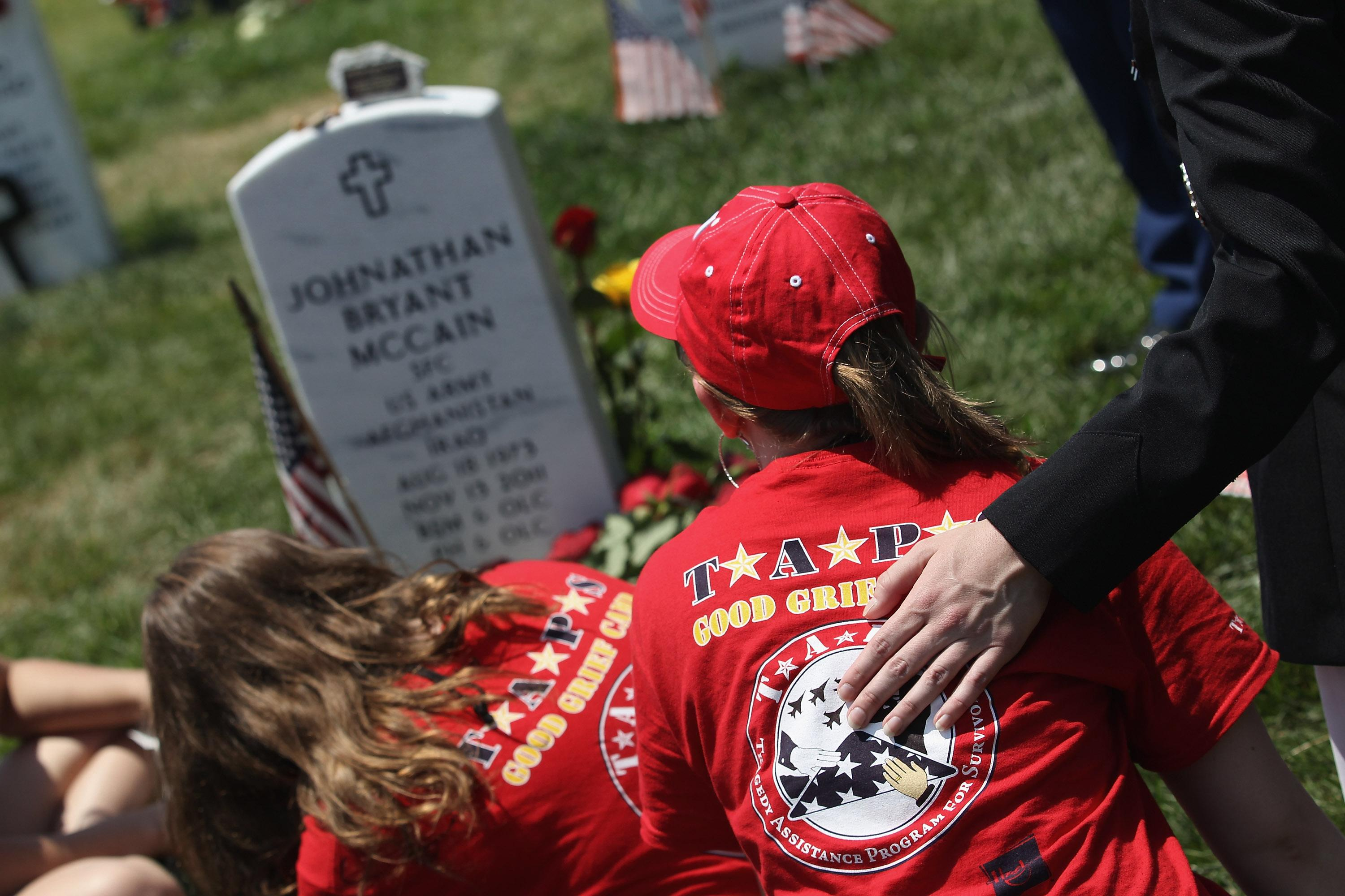 """Breanna McCain, 18, looks upon her father's grave at the National Cemetery on Memorial Day on May 28, 2012 in Arlington, Virginia. Her dad, Army SFC Johnathan McCain, was killed by a roadside bomb in Afghanistan in November 2011. Breanna came with her mother and three sisters to take part in a TAPS """"Good Grief Camp"""". Five hundred military children and teens, many of whom had a parent that was killed in the Afghan and Iraq wars, attended the annual four-day """"Good Grief Camp"""" in Arlington, VA and Washington, DC, which is run by TAPS (Tragedy Assistance Program for Survivors). The camp helped them learn coping skills and build relationships so they know they are not alone in the grief of their loved one. They met others of their own age group, learned together and shared their feelings, both through group activities and one-on-one mentors, who are all active duty or former military servicemembers. Some 1,200 adults, most of whom are grieving parents and spouses, also attend the National Military Survival Seminar held concurrently with the children's camp. The TAPS slogan is """"Remember the Love. Celebrate the Life. Share the Journey."""" (Photo by John Moore/Getty Images)"""
