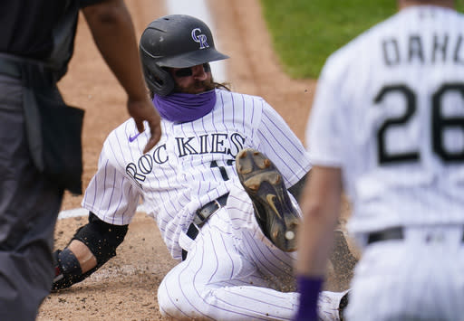 Colorado Rockies' Charlie Blackmon slides safely across home plate to score on a single hit by Josh Fuentes in the sixth inning of a baseball game Sunday, Sept. 20, 2020, in Denver. (AP Photo/David Zalubowski)