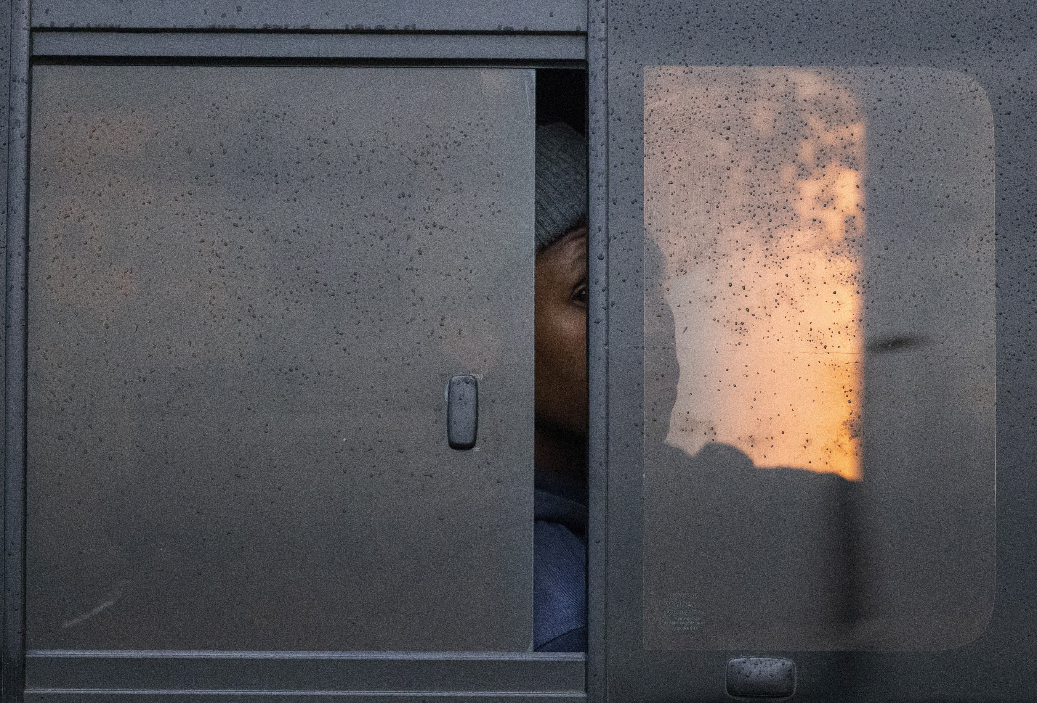 A passenger peeps through a window whilst sitting inside a minibus taxi during their journey to home in Kwa-Thema east of Johannesburg, South Africa, Tuesday, March 17, 2020. President Cyril Ramaphosa said all schools will be closed for 30 days from Wednesday and he banned all public gatherings of more than 100 people. South Africa will close 35 of its 53 land borders and will intensify screening at its international airports. For most people, the new COVID-19 coronavirus causes only mild or moderate symptoms. For some it can cause more severe illness. (AP Photo/Themba Hadebe)
