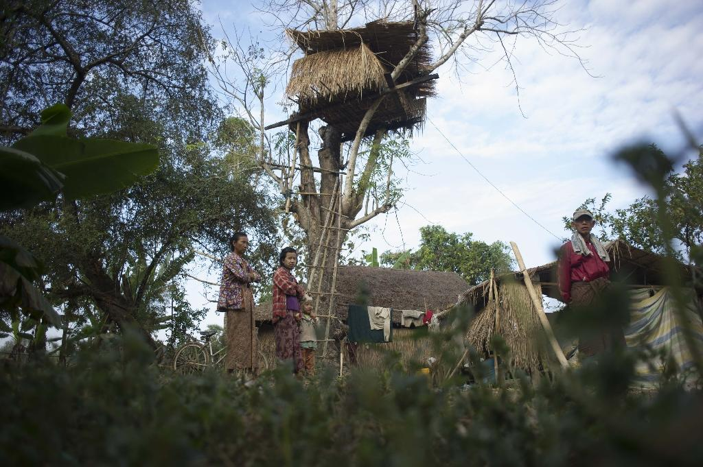 Residents stand near a tree house in the Kyauk Ye village on the outskirts of Yangon on January 14, 2016 (AFP Photo/Ye Aung Thu)