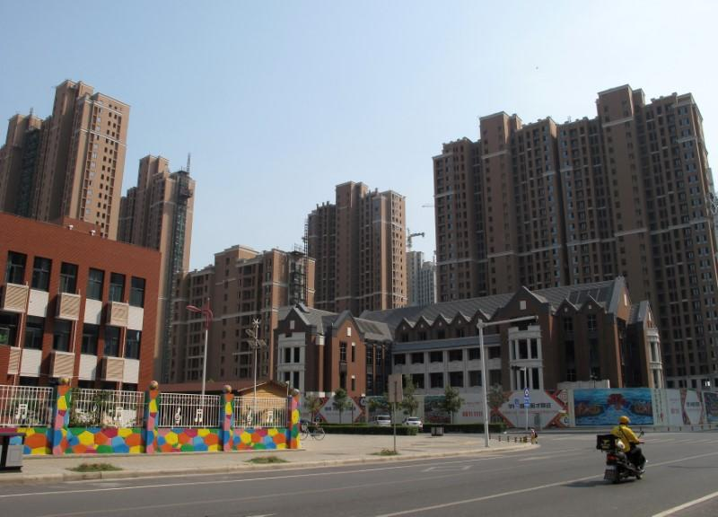 A food delivery man rides past residential buildings in Zhengzhou