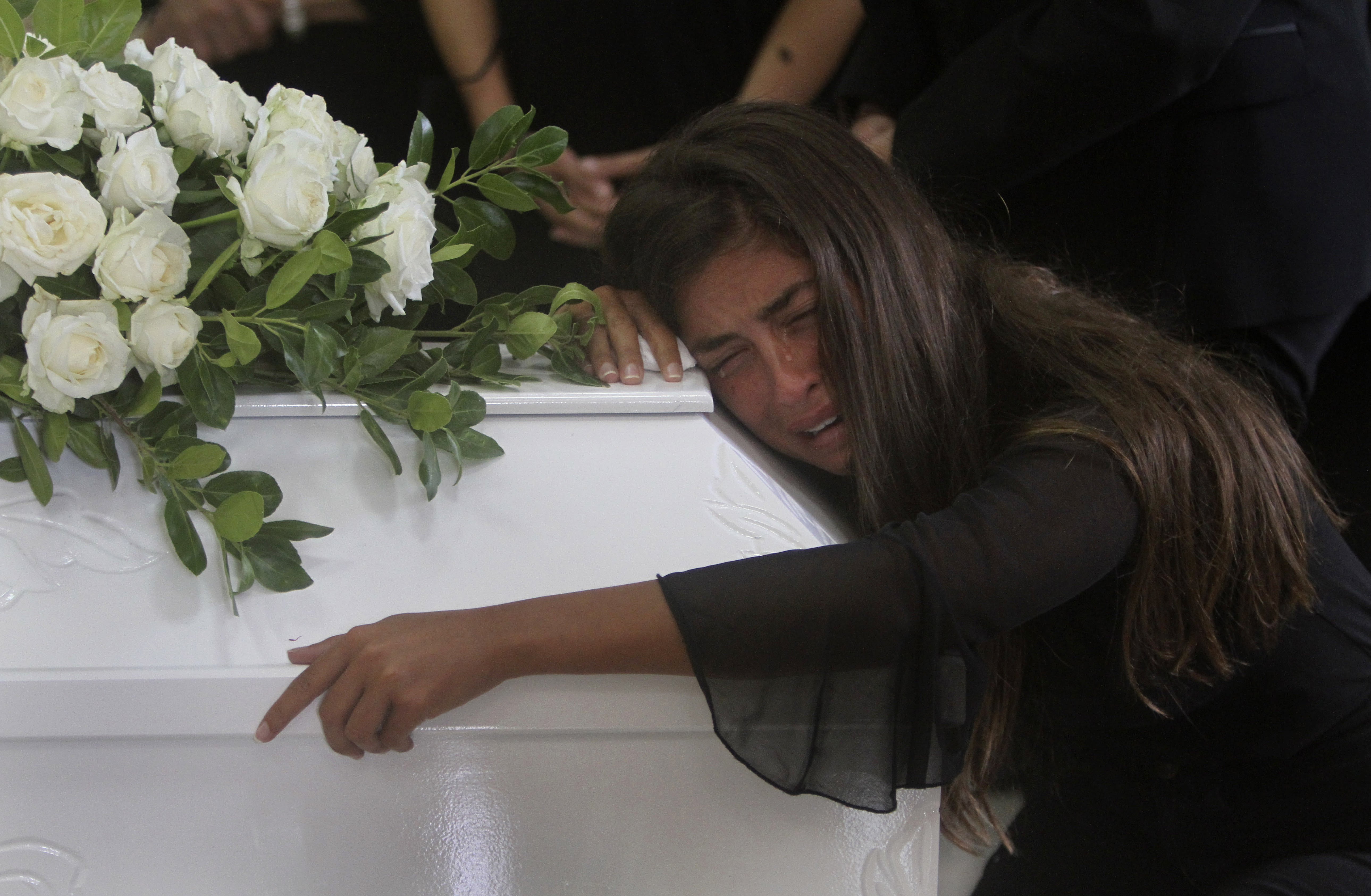 """The sister of Nicole al-Helou, who was killed by the explosion Tuesday that hit the seaport of Beirut, mourns on her coffin during her funeral, in Sarba village, southern Lebanon, Thursday, Aug. 6, 2020. French President Emmanuel Macron said an independent, transparent investigation into the massive explosion in Beirut is """"owed to the victims and their families"""" by Lebanese authorities. During Macron's visit to the city on Thursday, angry crowds approached him and the Beirut governor as they walked through a blast-torn street. (AP Photo/Mohammed Zaatari)"""