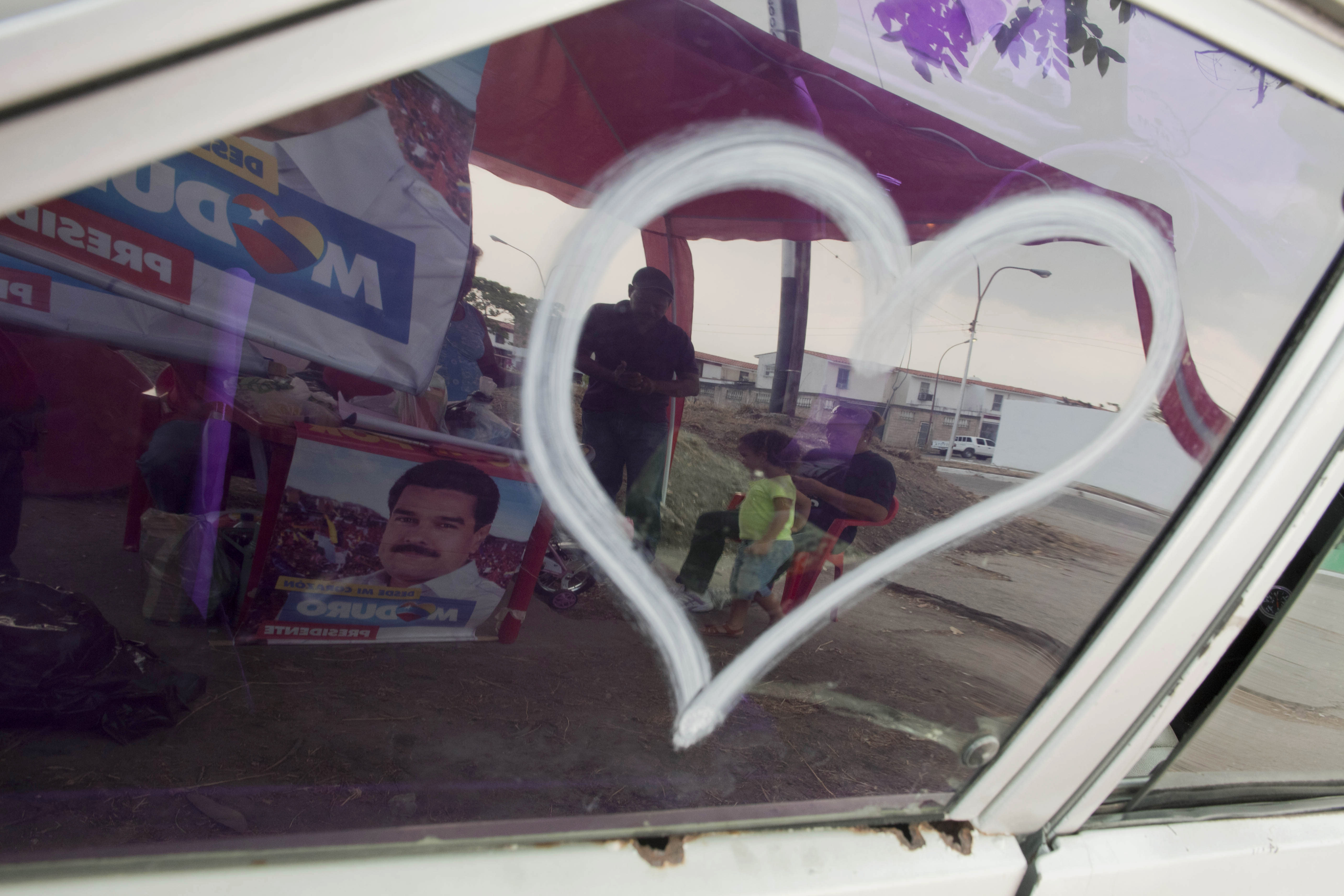 In this April 8, 2013 photo, supporters of the ruling party presidential candidate and acting President Nicolas Maduro are reflected in a car window in Valencia, Venezuela. Outside Venezuela's capital, power outages, food shortages and unfinished projects abound; important factors heading into Sunday's election to replace Chavez, who died last month after a long battle with cancer. Maduro, is favored to win, largely on the strength of Chavez's generous anti-poverty programs. But recent polls show that support for Maduro, Chavez's hand-picked successor, may be eroding. (AP Photo/Ramon Espinosa)
