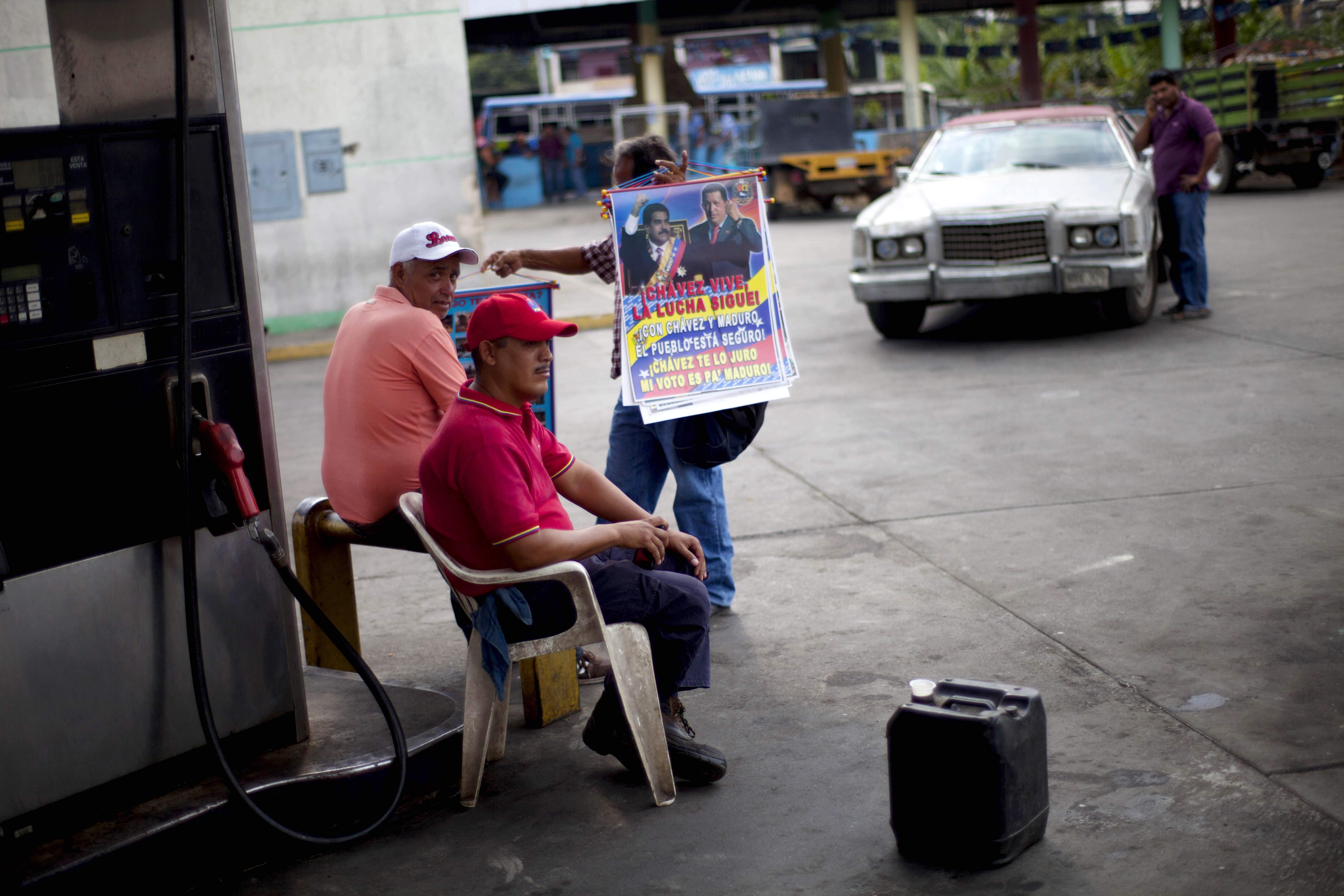 In this April 8, 2013 photo, street vendor Jose Gonzalez, 62, tries to persuade gas stations workers to buy some posters featuring Venezuela's late President Hugo Chavez and acting President Nicolas Maduro, in Tacarigua, Venezuela. Outside Venezuela's capital, power outages, food shortages and unfinished projects abound; important factors heading into Sunday's election to replace Chavez, who died last month after a long battle with cancer. Polls show that support for Maduro, Chavez's hand-picked successor, may be eroding and constant power outages are a testament to the neglect many Venezuelans consider inexcusable in this major oil-producing state. (AP Photo/Ramon Espinosa)