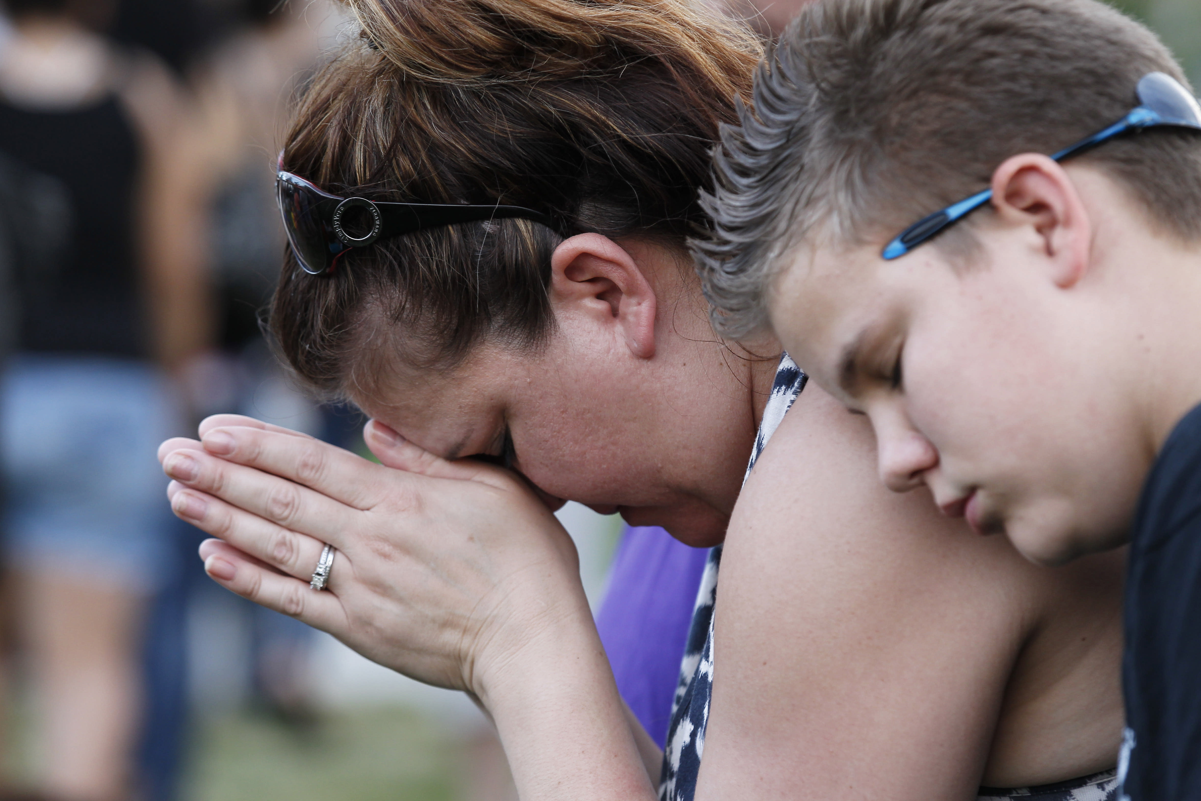 """Dylan Bowen, 13, right, holds onto his mother Lorri Hastings, as they pray, Sunday, July 22, 2012 in Aurora, Colo., during a prayer vigil for the victims of Friday's mass shooting at a movie theater. Twelve people were killed and dozens were injured in a shooting attack early Friday at the packed theater during a showing of the Batman movie, """"The Dark Knight Rises."""" Police have identified the suspected shooter as James Holmes, 24. (AP Photo/Alex Brandon)"""