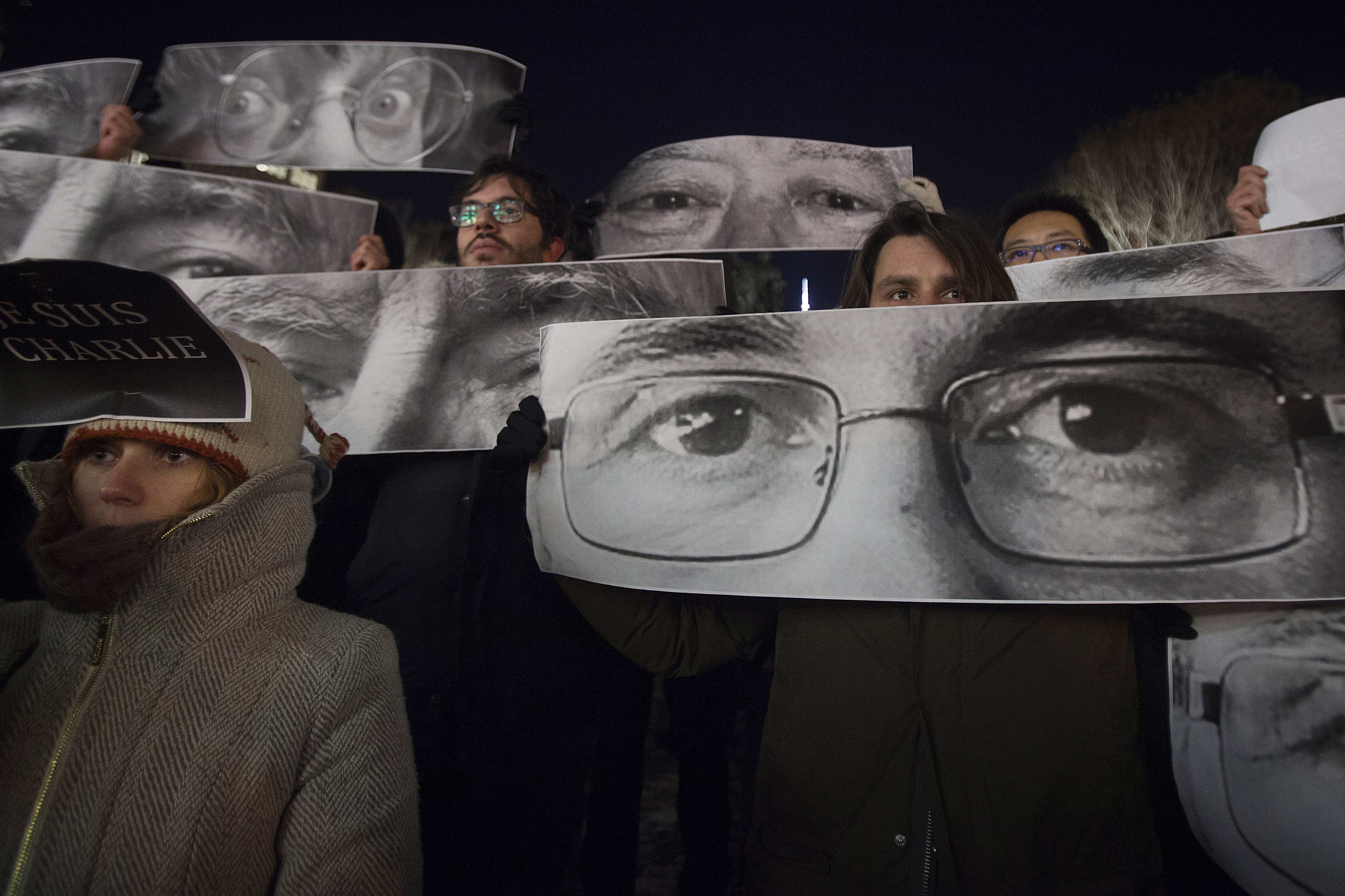People hold up posters, which include Charlie Hebdo Editor Stephane Charbonnier (front), a cartoonist known as Charb, and Jean Cabut (back L), a cartoonist known as Cabu, during a vigil to pay tribute to the victims of a shooting, by gunmen at the offices of weekly satirical magazine Charlie Hebdo in Paris, in the Manhattan borough of New York January 7, 2015. Hooded gunmen stormed the Paris offices of the weekly satirical magazine known for lampooning Islam and other religions, shooting dead at least 12 people, including two police officers, in the worst militant attack on French soil in decades. REUTERS/Carlo Allegri (UNITED STATES - Tags: CIVIL UNREST CRIME LAW)
