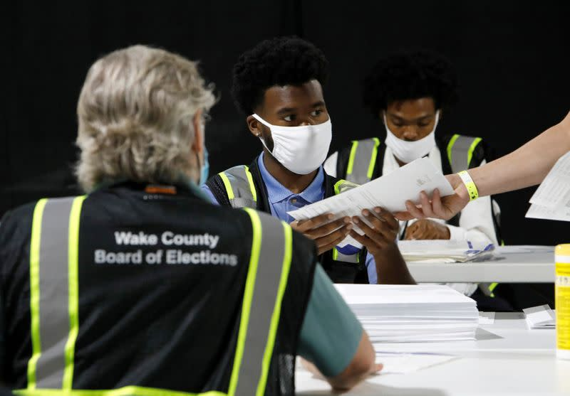 FILE PHOTO: Poll workers prepare absentee ballots for the general election in Raleigh