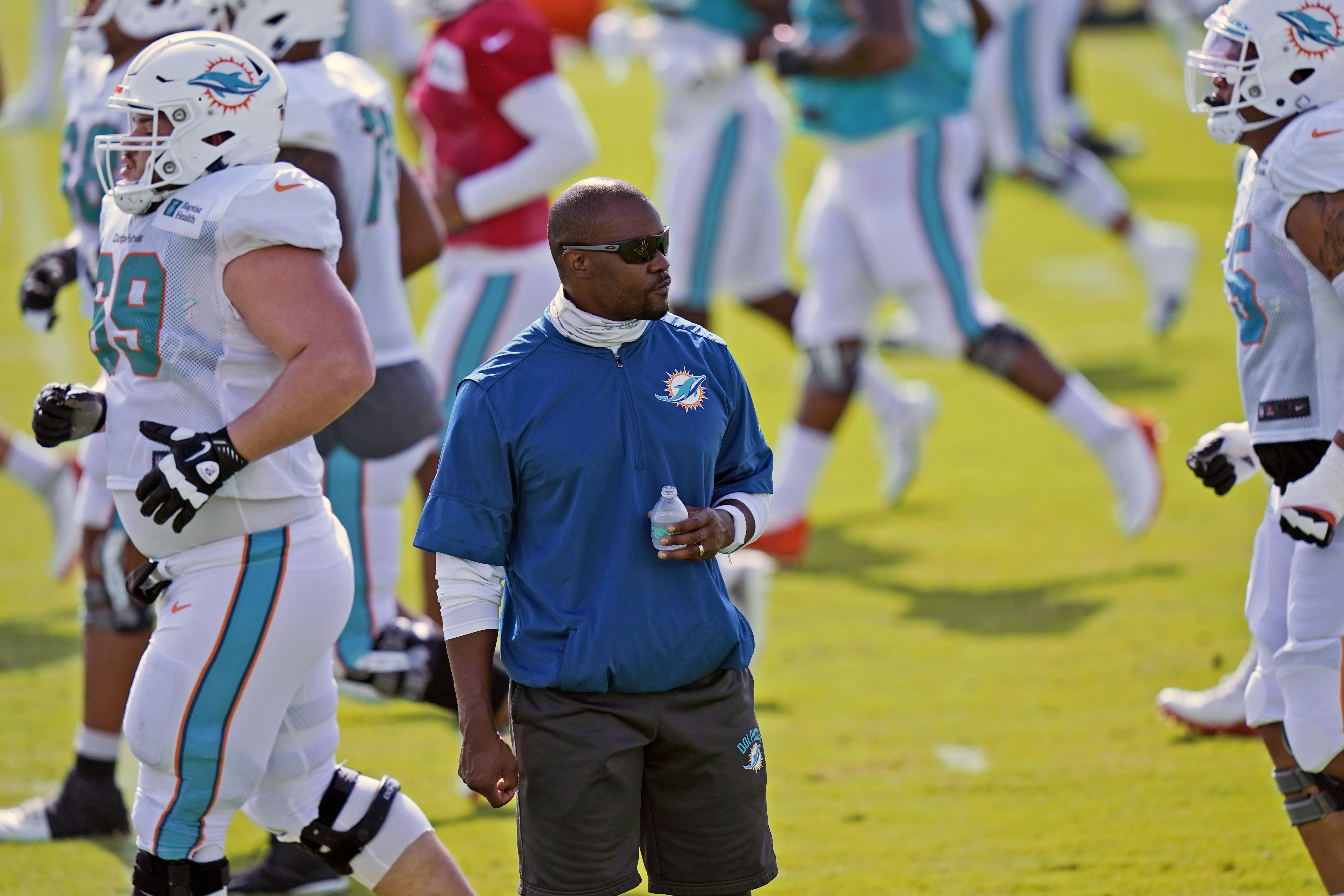 FILE - In this Aug. 21, 2020, file photo, Miami Dolphins head coach Brian Flores watches practice at the NFL football team's training facility in Davie, Fla. The Dolphins roster appears significantly upgraded by the draft and free agency, but the coronavirus pandemic curtailed offseason training. As a result, the Dolphins' 2020 season might be similar to 2019, when they were much better in December than in September. (AP Photo/Lynne Sladky, File)