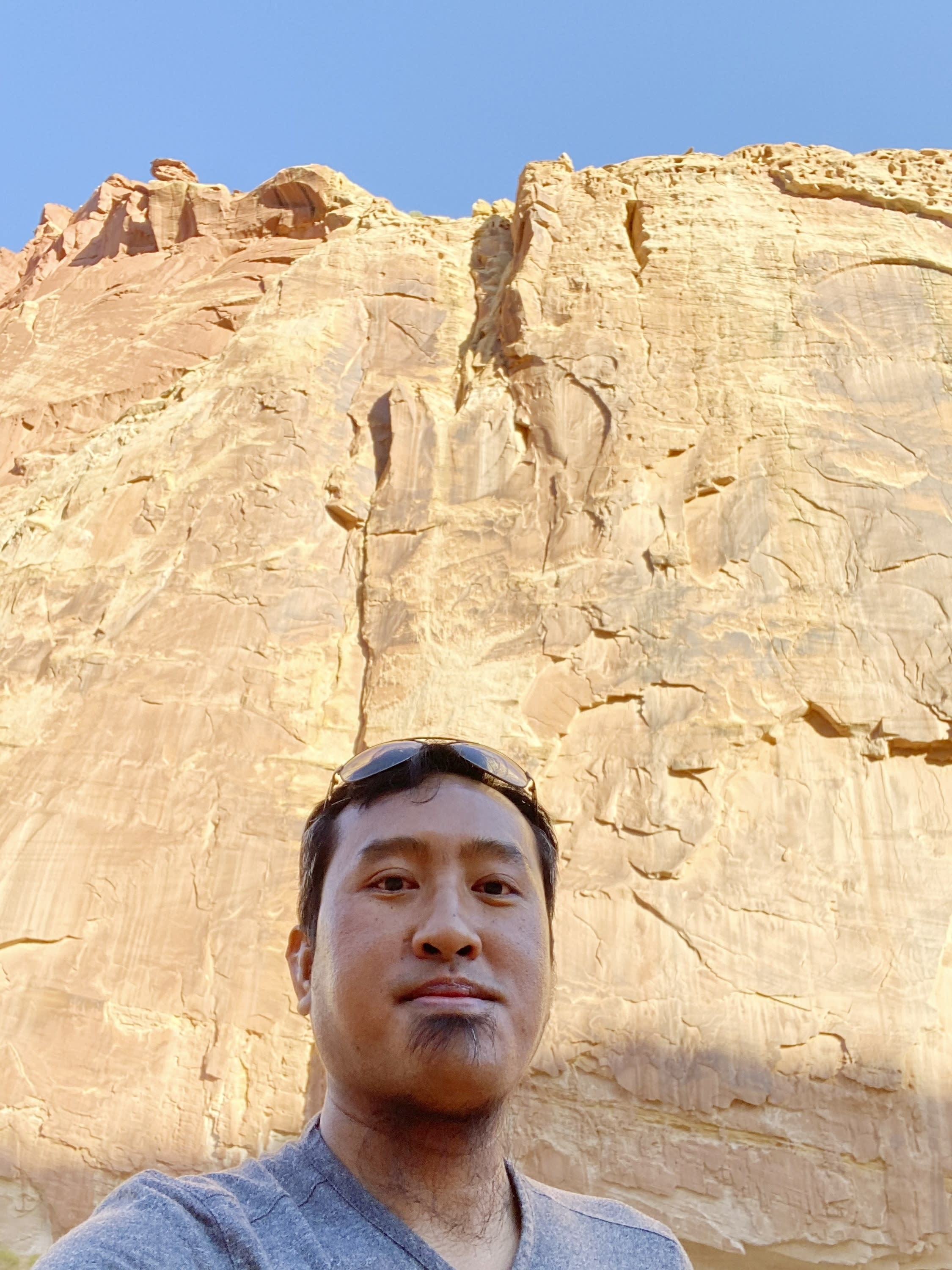 In this Aug. 15, 2020, photo provided by Lian Kual, resettled refugee Kual, originally from Myanmar, stands against a rock wall in the Capitol Reef National Park in Utah, the state where he now lives. Kual, who was naturalized earlier this year, said he is looking forward to voting in the U.S. presidential election after growing up in a country that had no democratic culture during decades of military rules. (Lian Kual via AP)