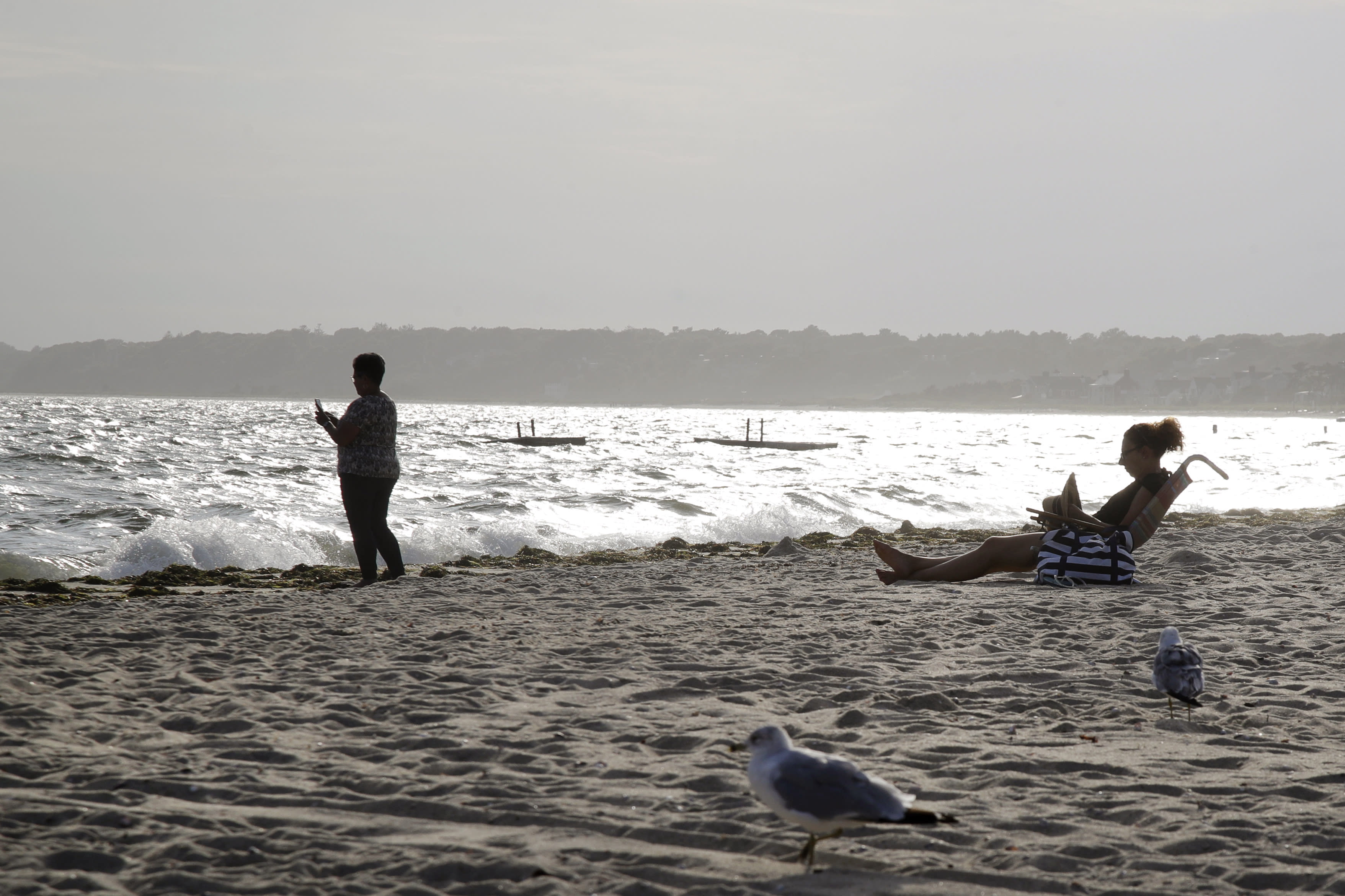 In this Aug. 21, 2019 photo, people enjoy the view at Covell Beach in Centerville, Mass. Vineyard Winds' proposed buried energy cables would stretch from offshore wind turbines, through the ocean, under the sand and parking lot at Covell Beach, to a landing point where the cables would then extend to a grid connection inland. But as Trump has made clear how much he hates wind turbines, all the offshore wind projects, including the nation's first utility-scale offshore wind project, an 84 turbine, $2.8 billion wind farm slated to rise 15 miles off Martha's Vineyard, have stalled. (AP Photo/Elise Amendola)